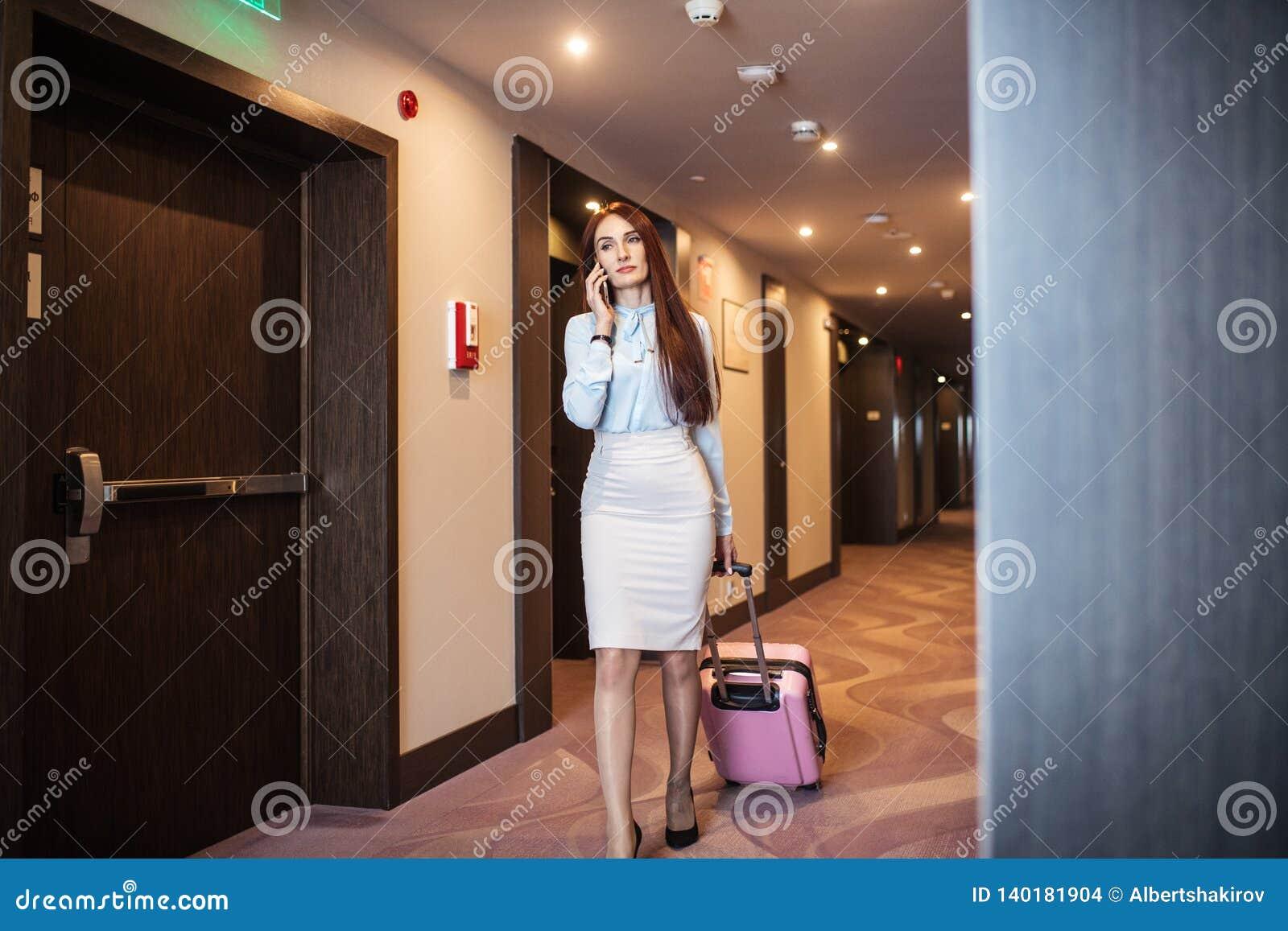 Elegant kvinna som talar på den smarta telefonen, medan lämna hotellet med resväskan