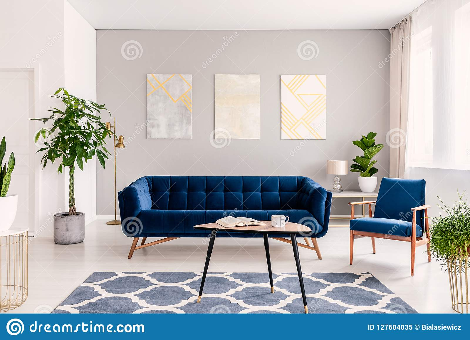Elegant living room interior with a set of dark blue sofa and armchair. Gold and silver contemporary paintings on the background w