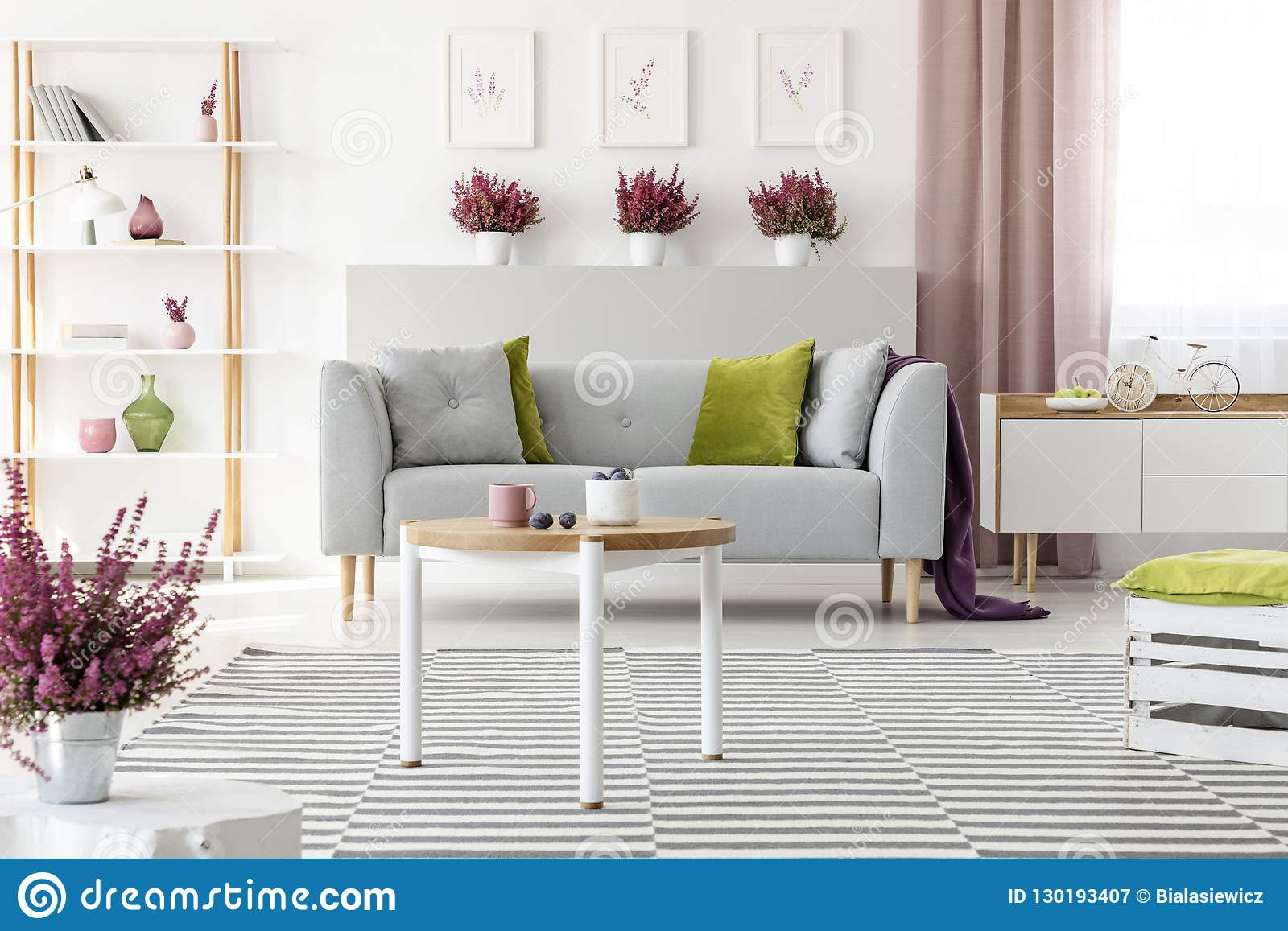 Elegant living room with white furniture, stylish wooden coffee table, patterned rug, grey couch with pillows and heather