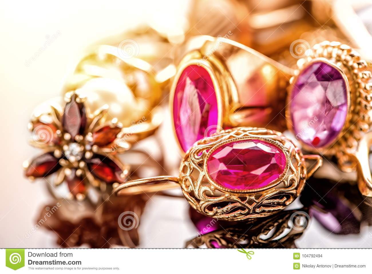 Elegant luxury composition of gold jewelry with ring with red amethyst and ruby gemstone and diamonds on light background close-up
