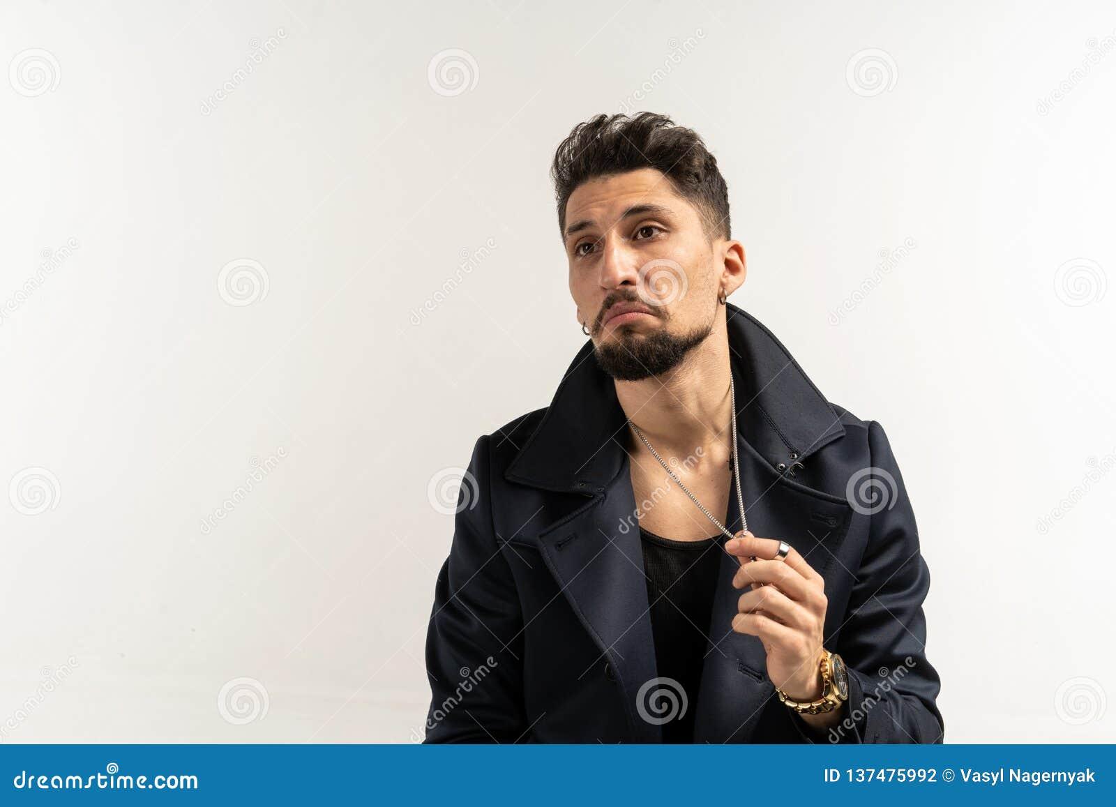 Elegant man with beard in black jacket posing on white wall