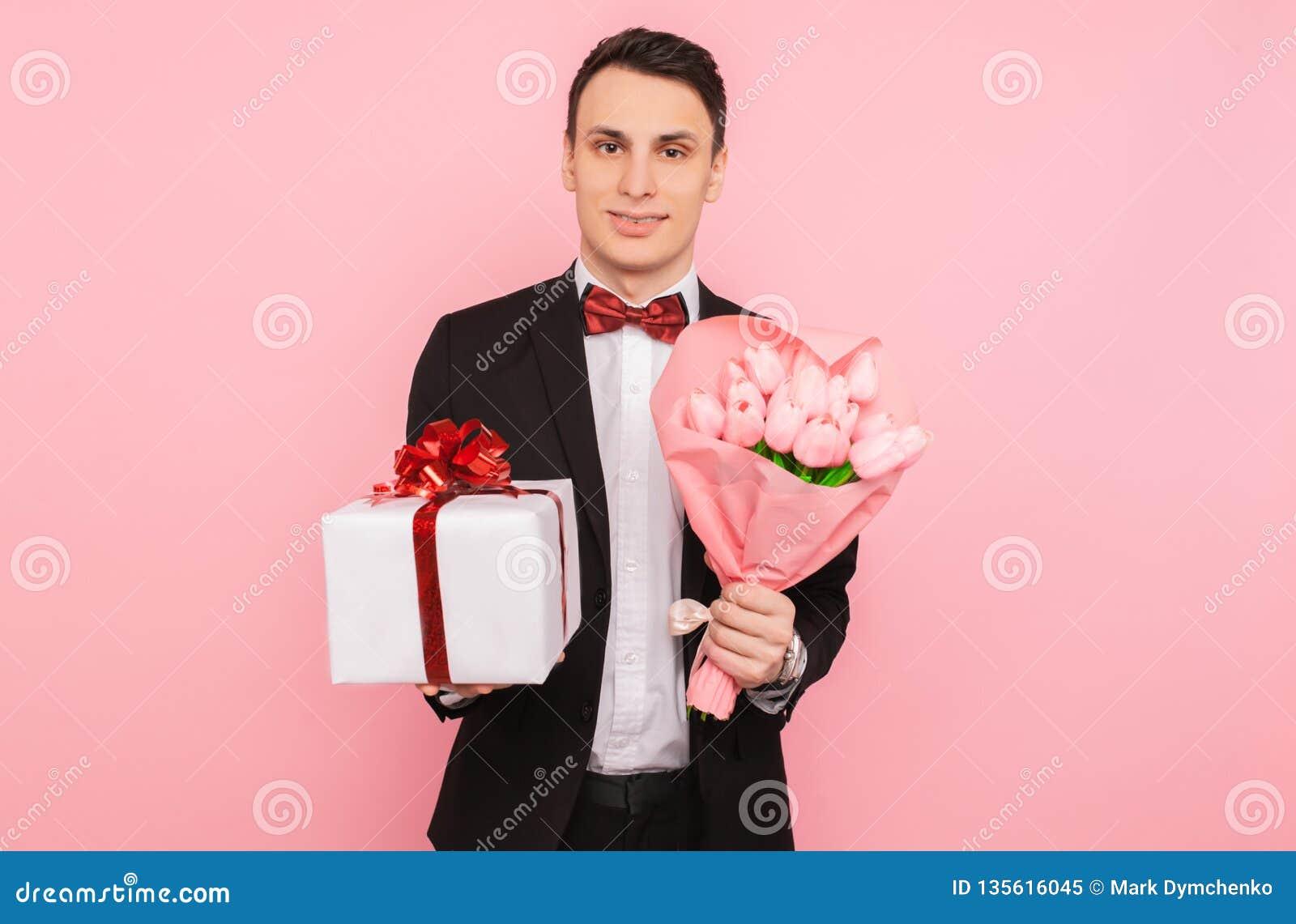 Elegant man, i en dräkt, med en bukett av blommor och en gåvaask, på en rosa bakgrund, begreppet av kvinnors dag