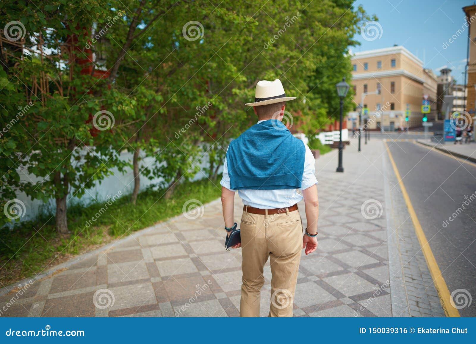Elegant man som går på en stadsgata