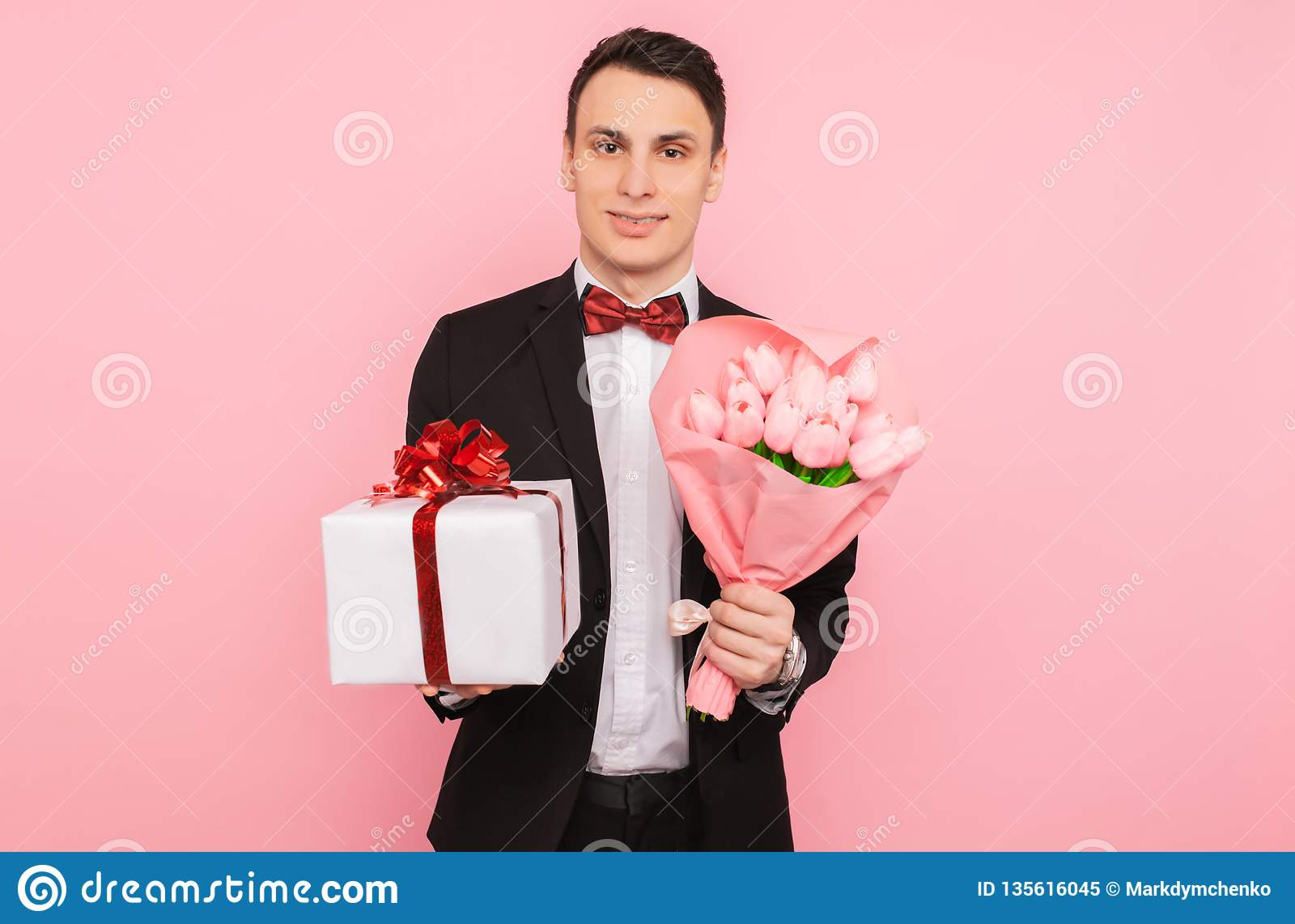 Elegant man, in a suit, with a bouquet of flowers, and a gift box, on a pink background, the concept of women`s day