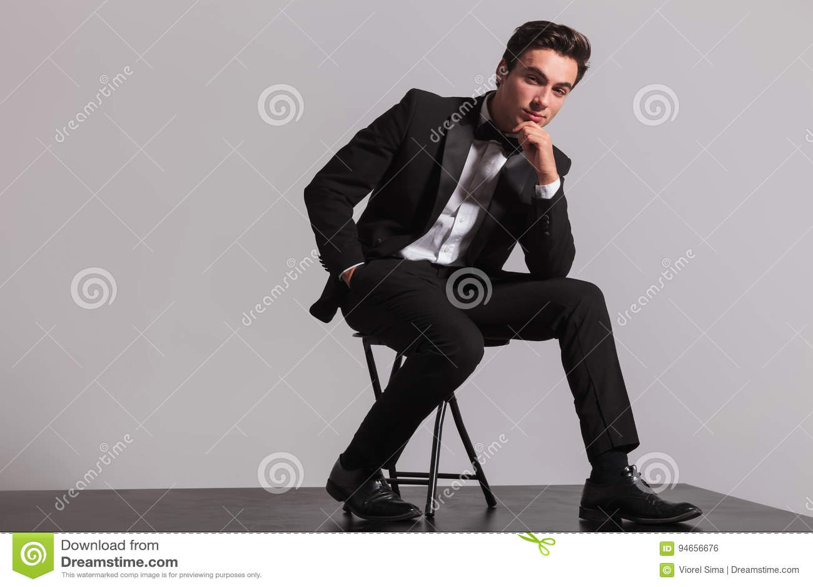 elegant man in tuxedo is sitting and thinking stock photo - image