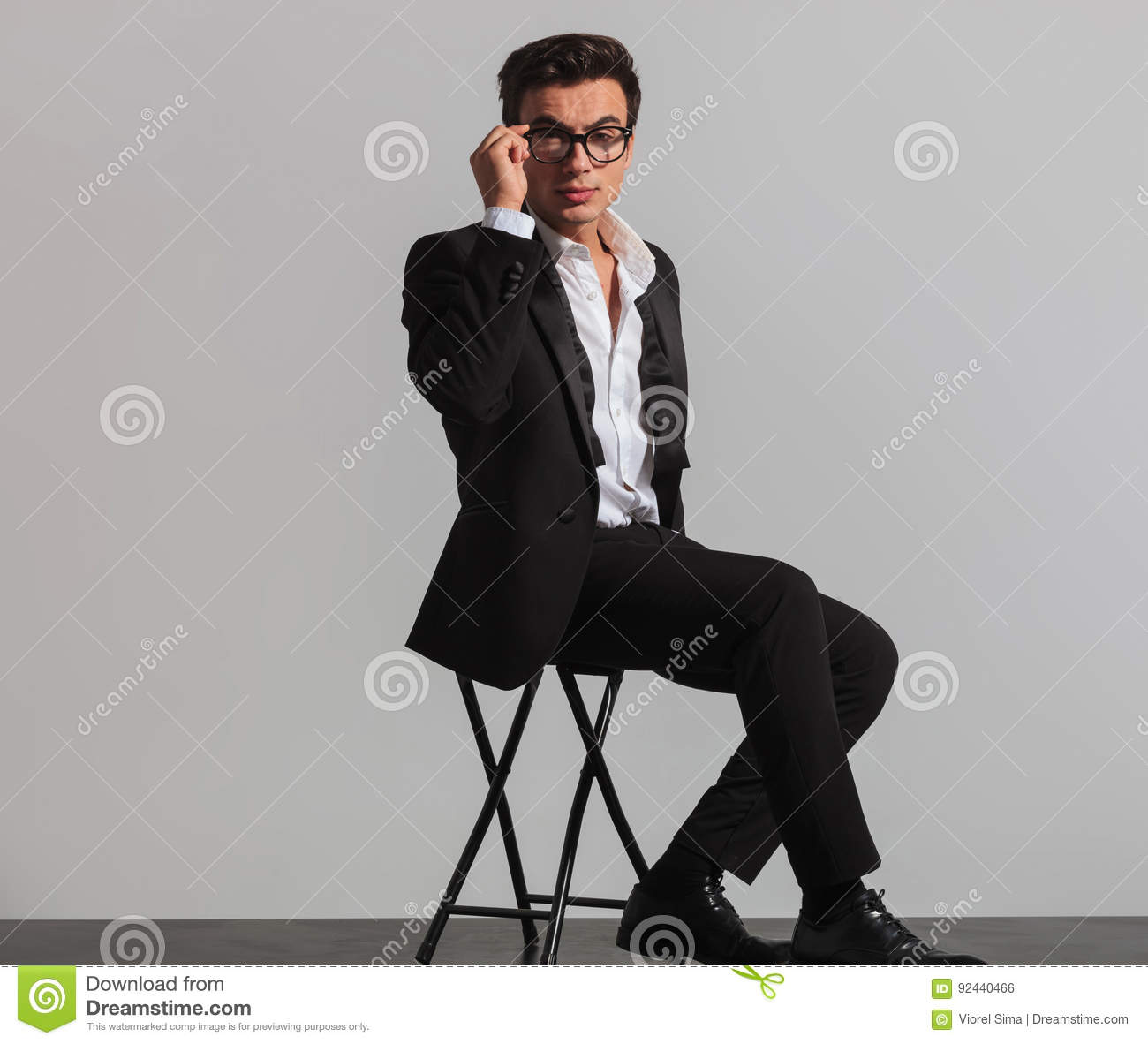 751792703613 Seated elegant man in tuxedo and undone bowtie fixing his glasses in studio