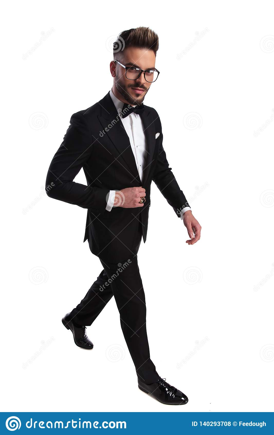 Elegant man walking while arranging his jacket