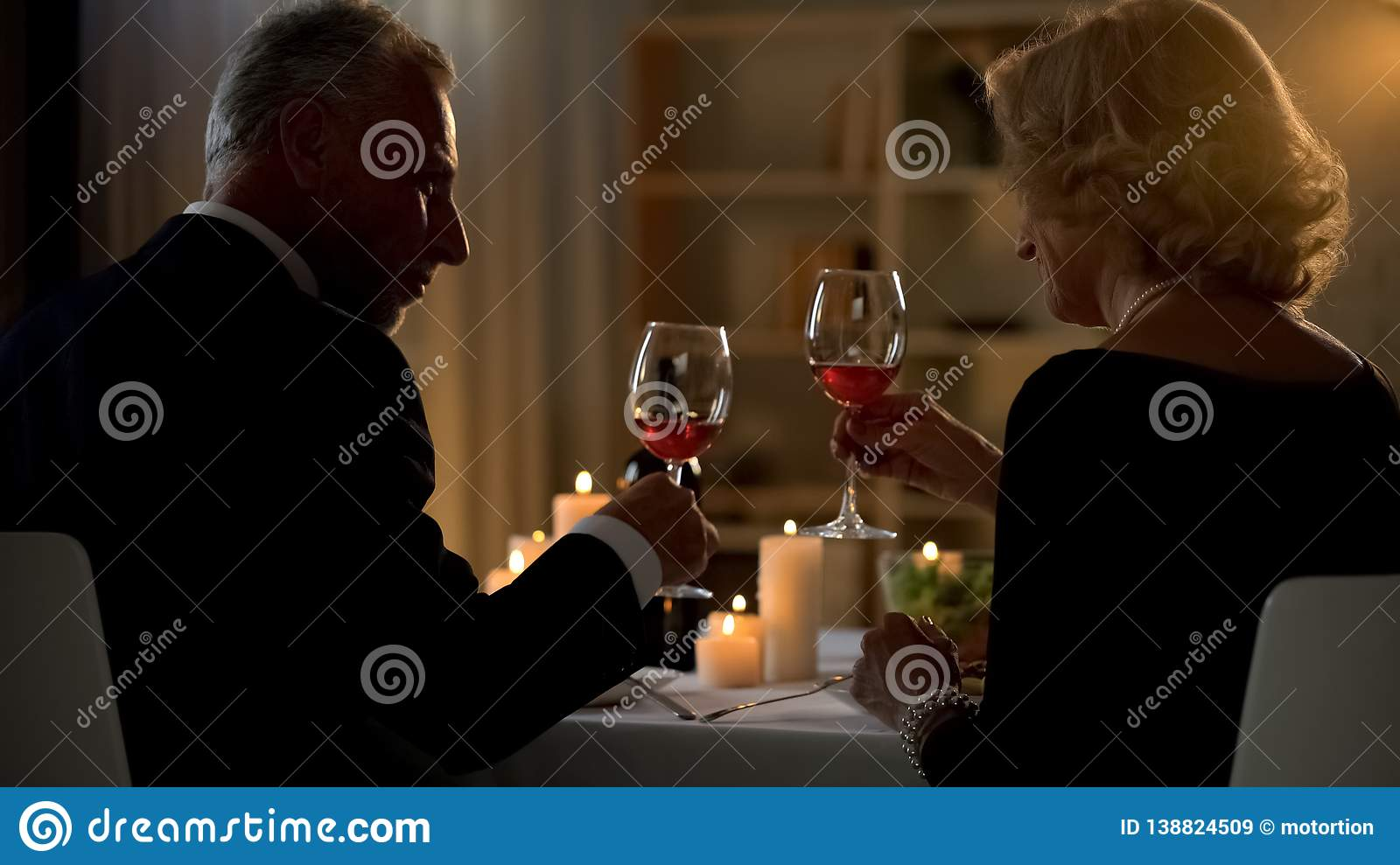 Elegant man and woman holding red wine glasses, senior couple on date, love