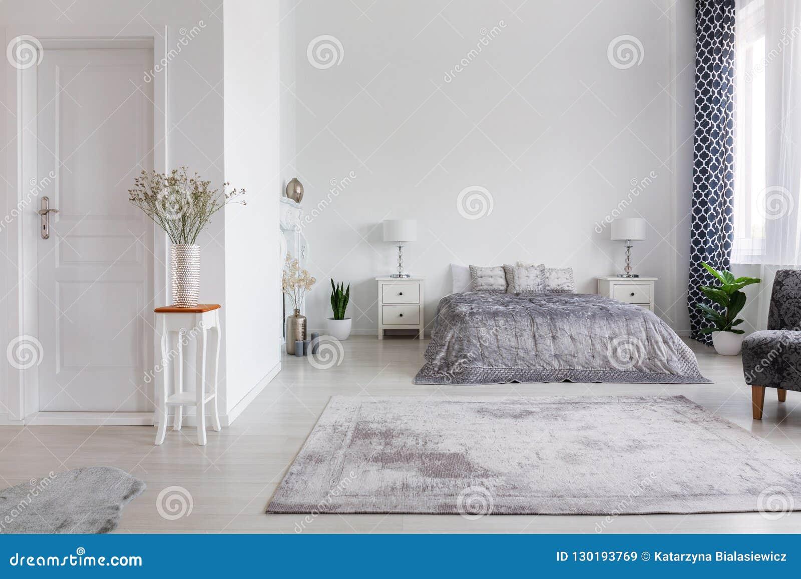 Elegant New York stilsovrum med bekväm säng, verkligt foto med kopieringsutrymme på den vita väggen