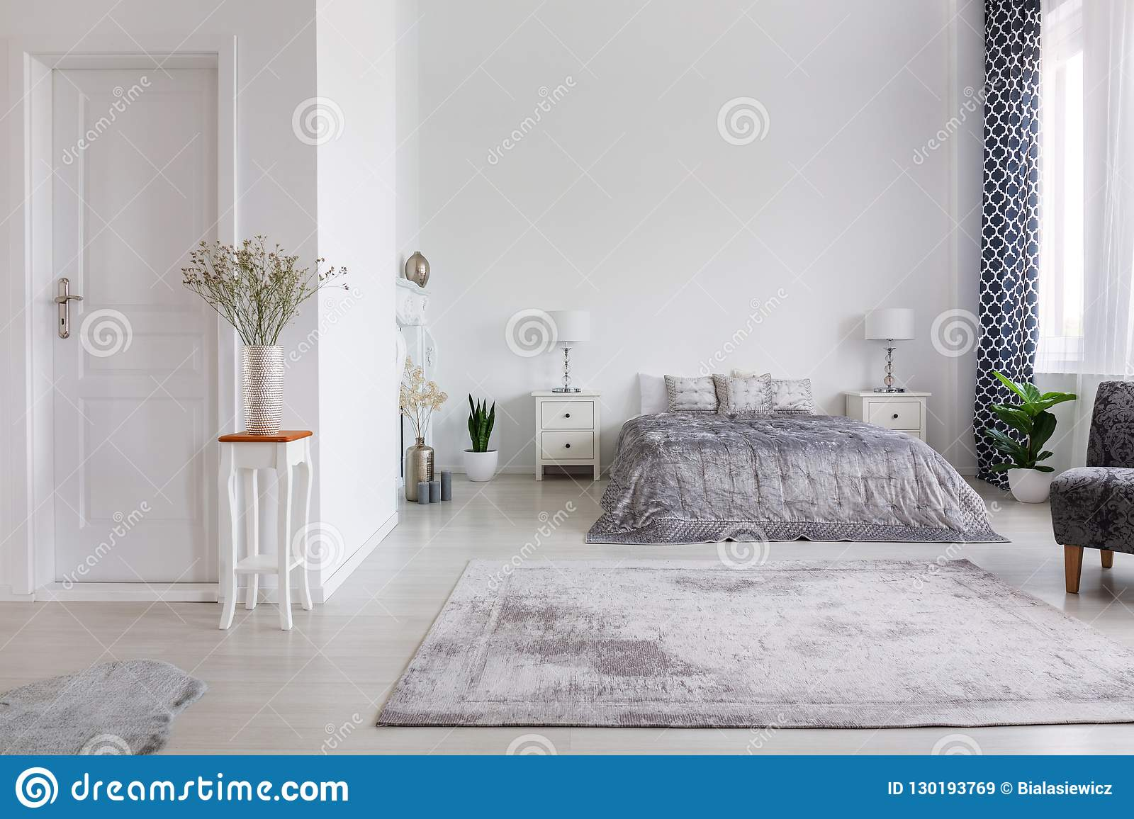 Elegant new york style bedroom with comfortable bed, real photo with copy space on the white wall