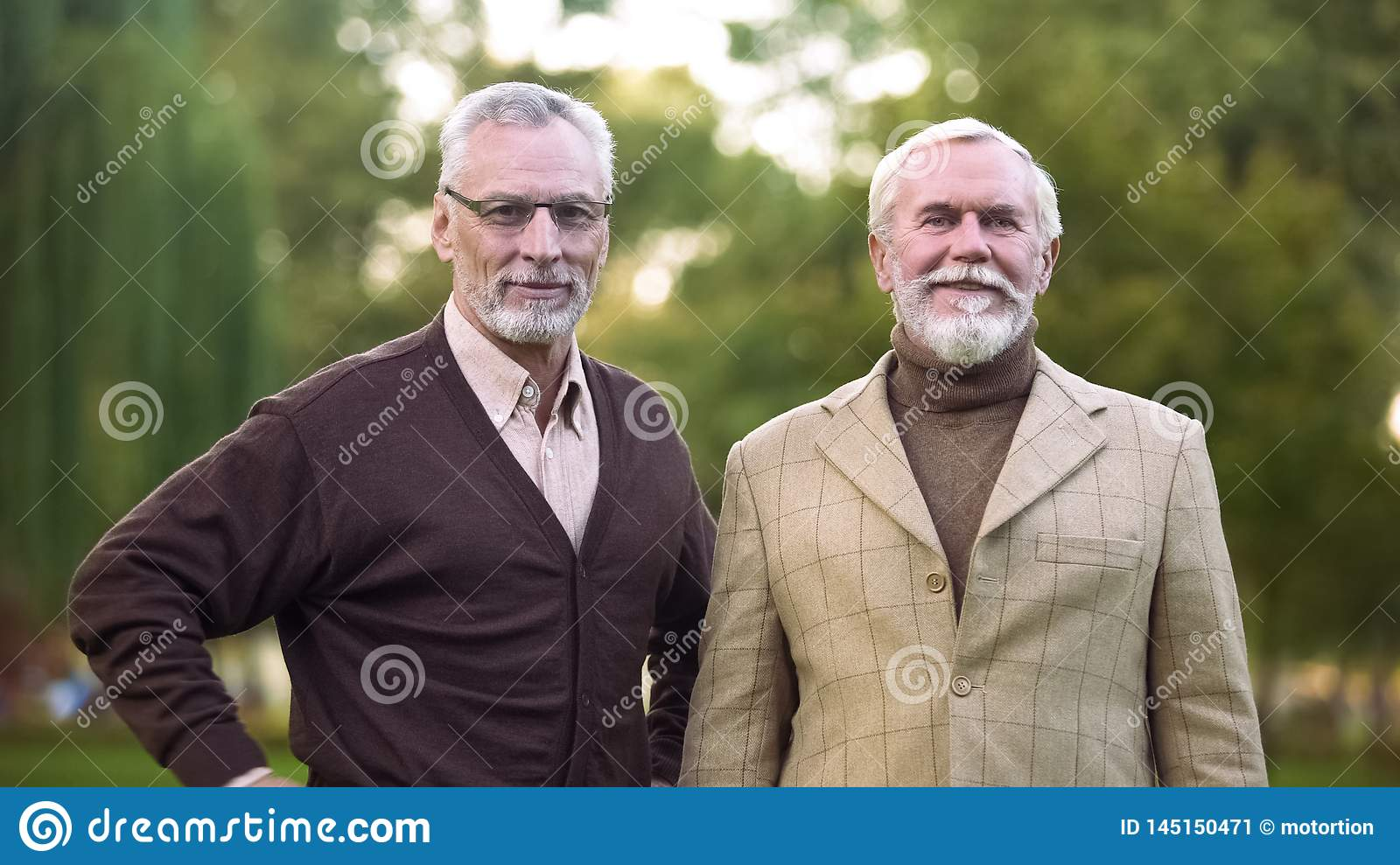 Elegant old men looking camera and smiling, happy retirement, success and wealth