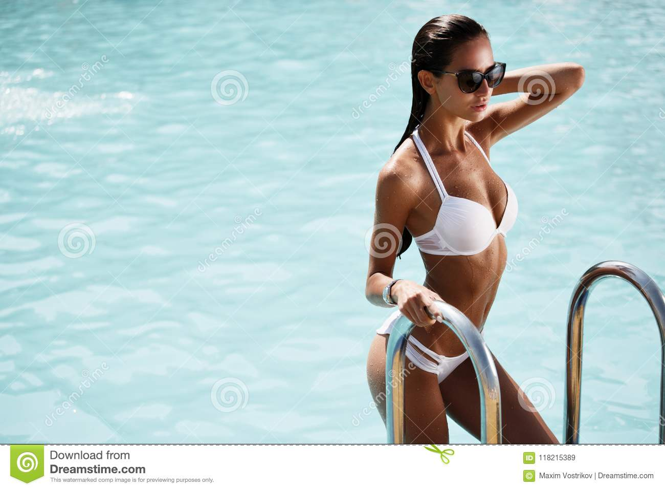 Elegant woman in the white bikini on the sun-tanned slim and shapely body is posing near the swimming pool
