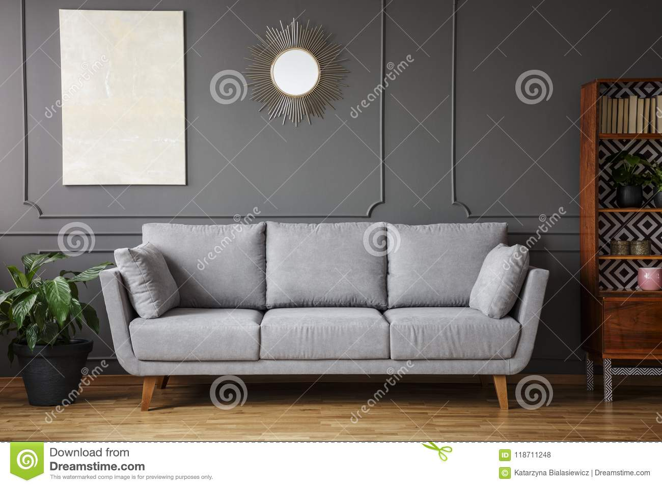 Elegant sofa between a plant a wooden cupboard in a living room interior with a painting and mirror on the wall in a living room