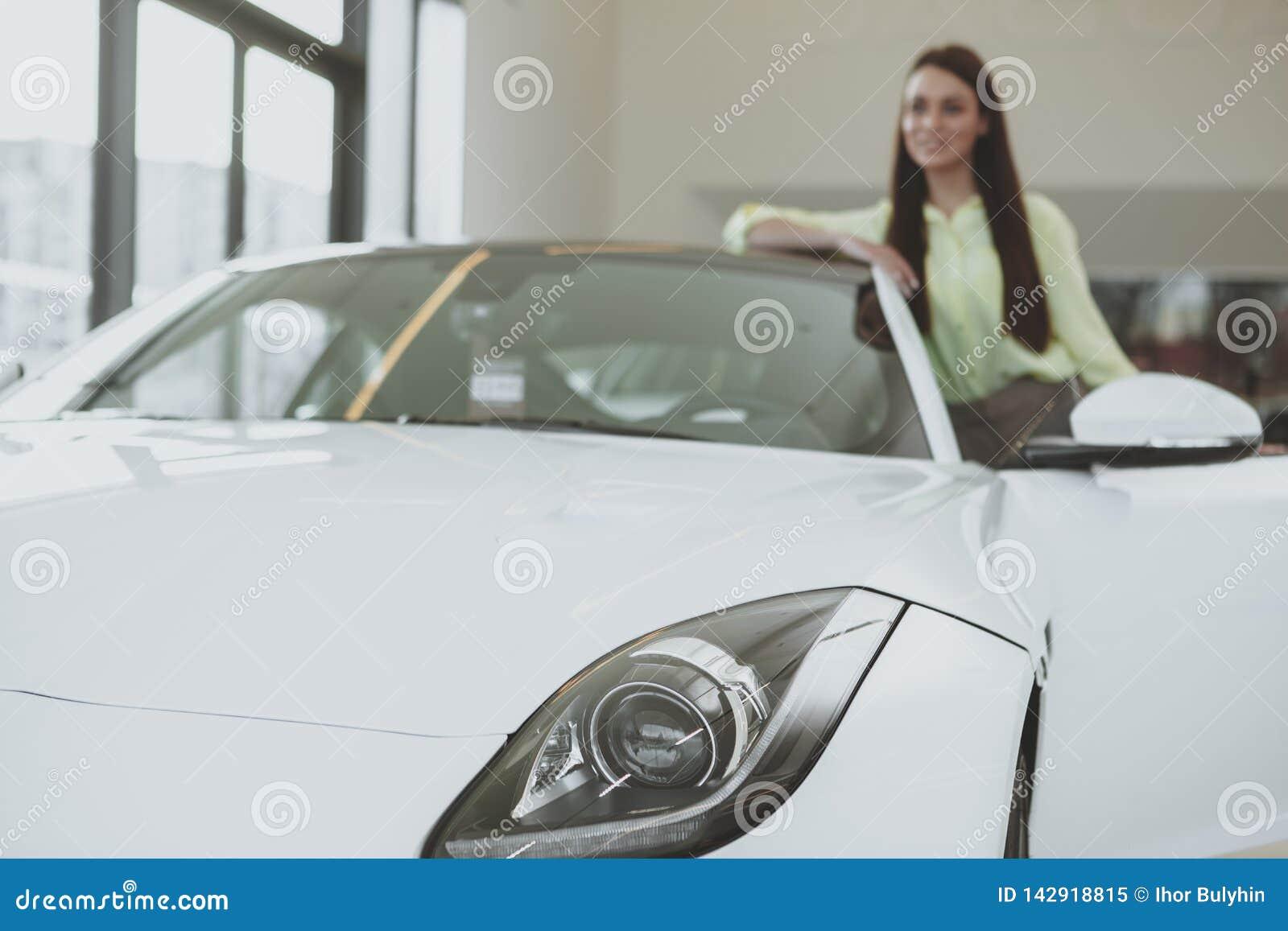 Elegant ung kvinna som köper den nya bilen på återförsäljaren