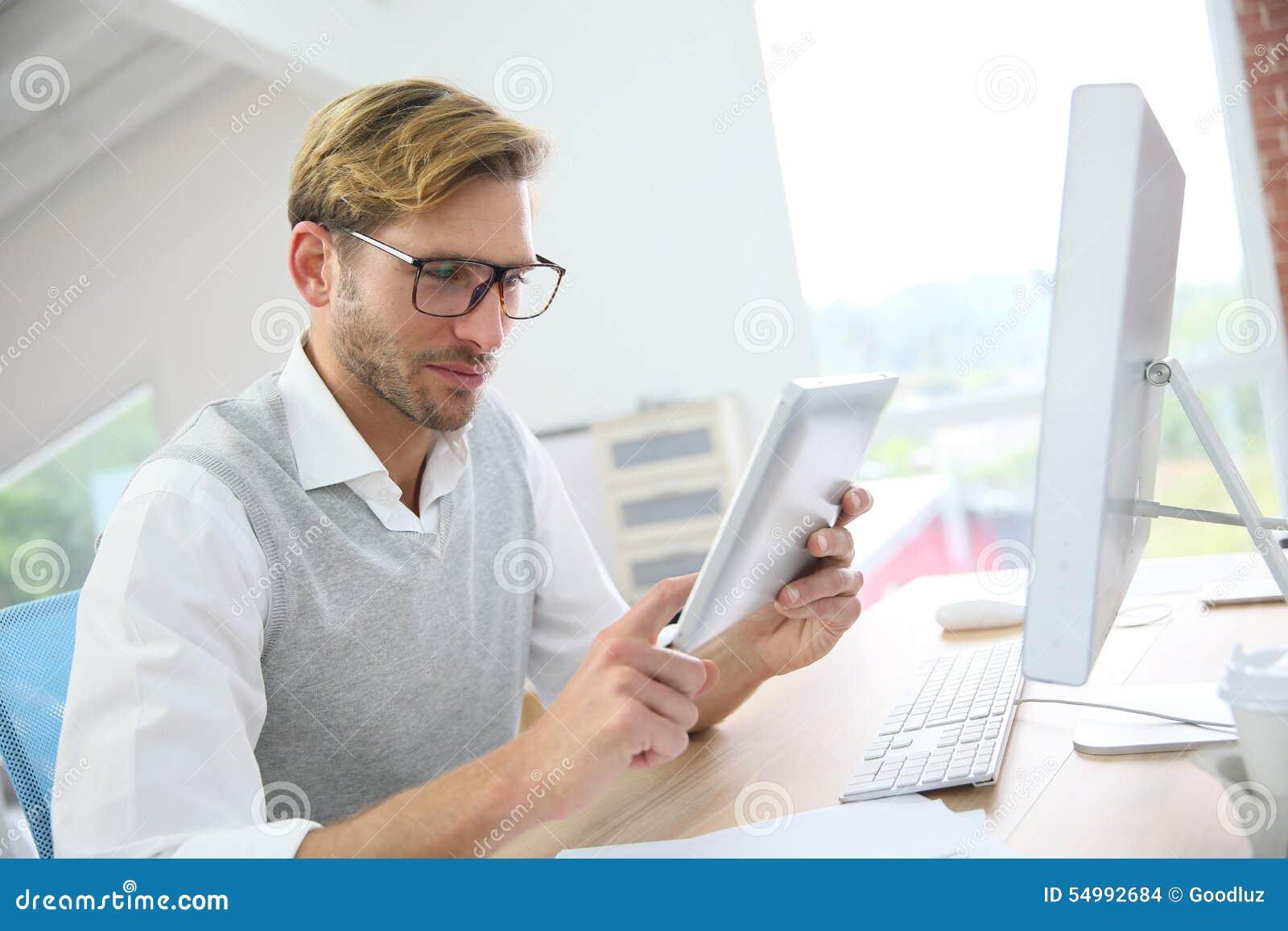Elegant ung man på kontoret som arbetar på minnestavlan