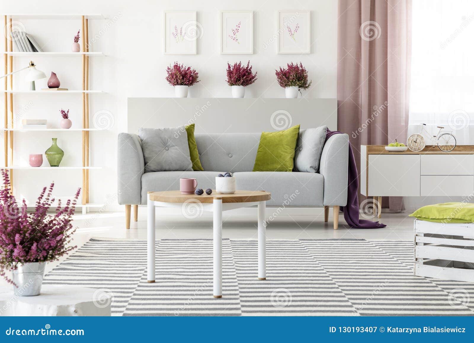 Elegant vardagsrum med vitt möblemang, den stilfulla träkaffetabellen, den mönstrade filten, den gråa soffan med kuddar och ljung