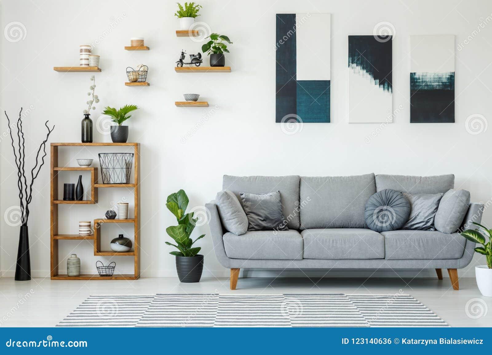 Elegant vardagsruminre med en grå soffa, trähyllor, p