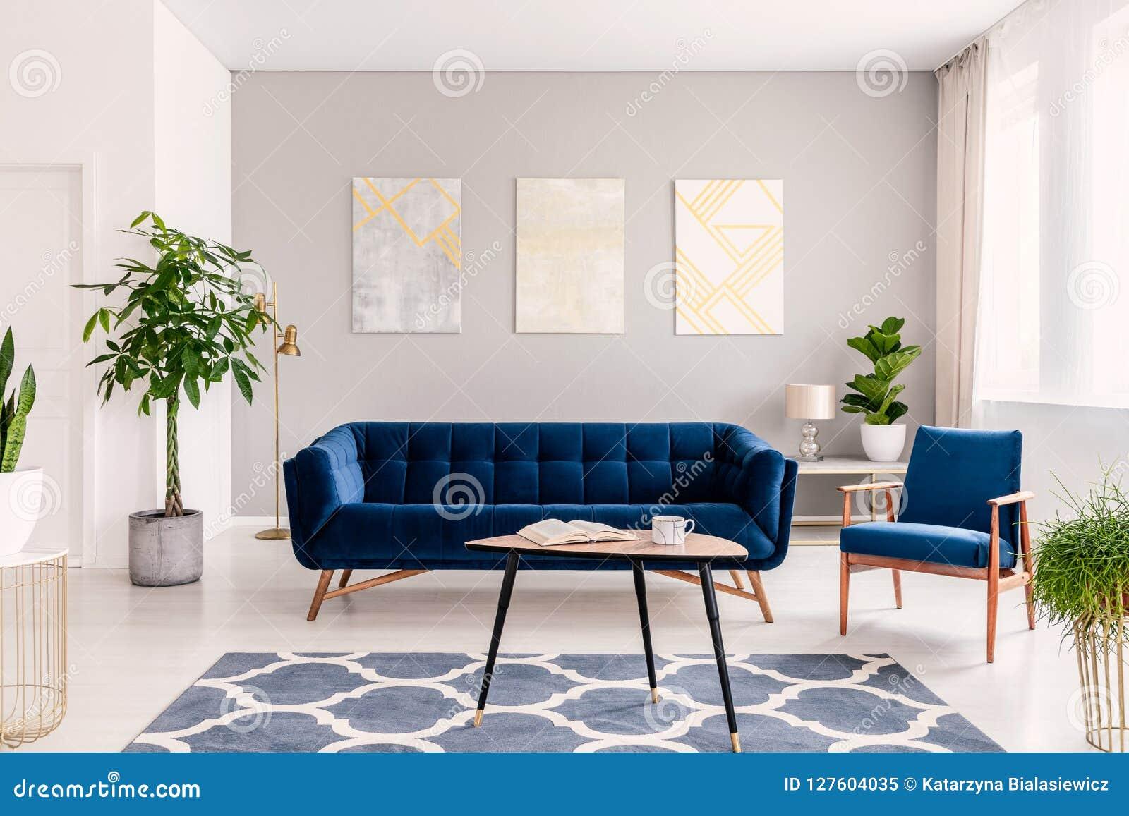 Elegant vardagsruminre med en uppsättning av mörker - blå soffa och fåtölj Moderna målningar för guld och för silver på bakgrunde