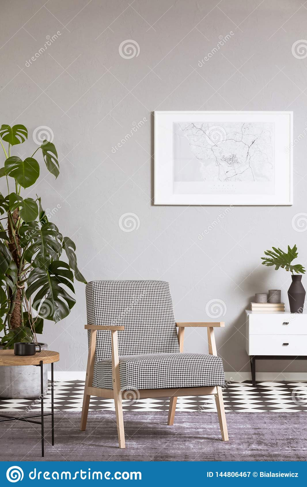 Elegant vintage armchair in living room interior with painting on the wall