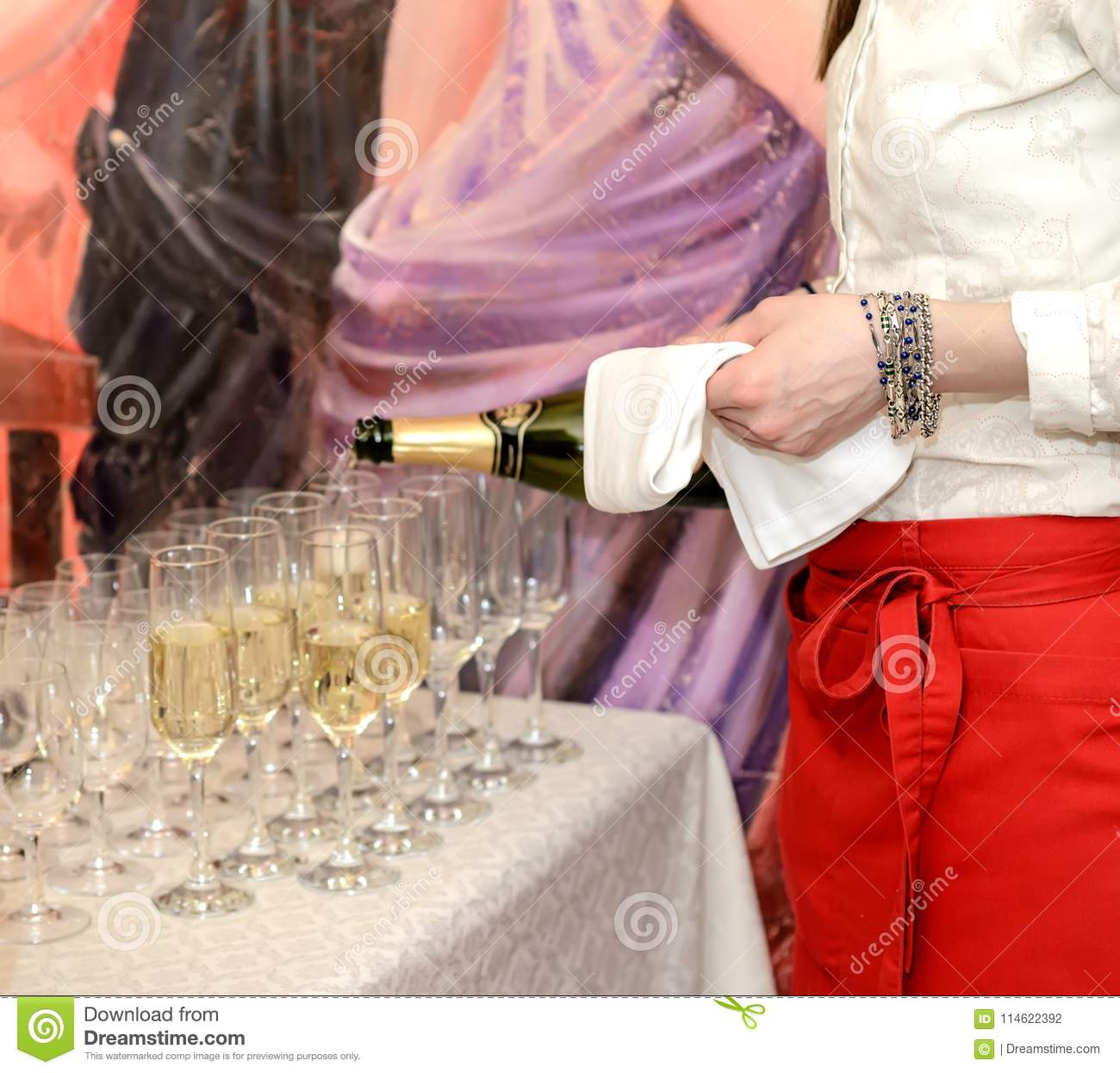 Elegant waitress pours champagne into group of glasses