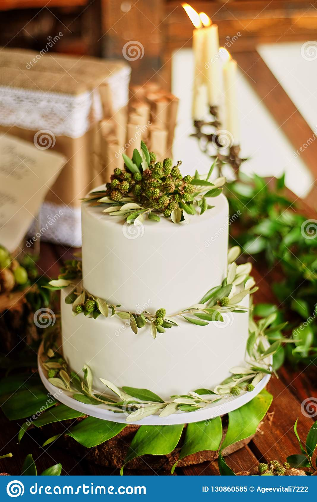 Elegant wedding cake with flowers and decor from green berries. Vegetarian sweets