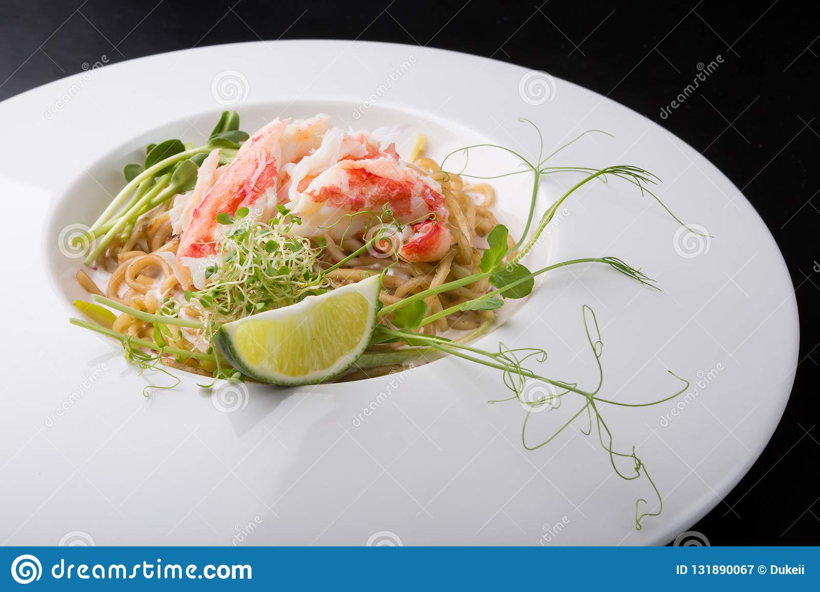 Elegant white crab meat noodles salad. Served with lime royalty free stock photography