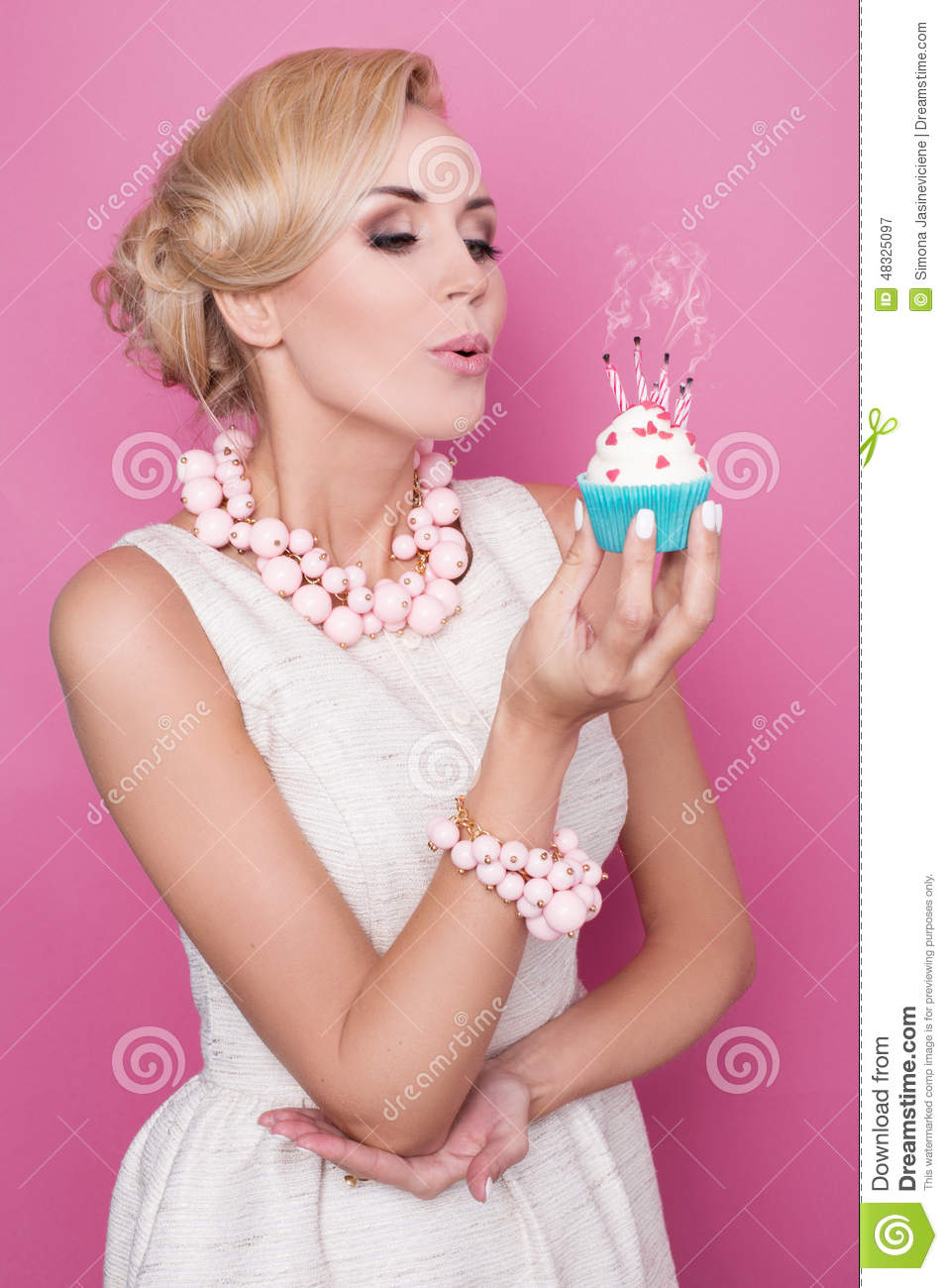 Elegant Woman Blowing Out Candles On Birthday Cake Stock