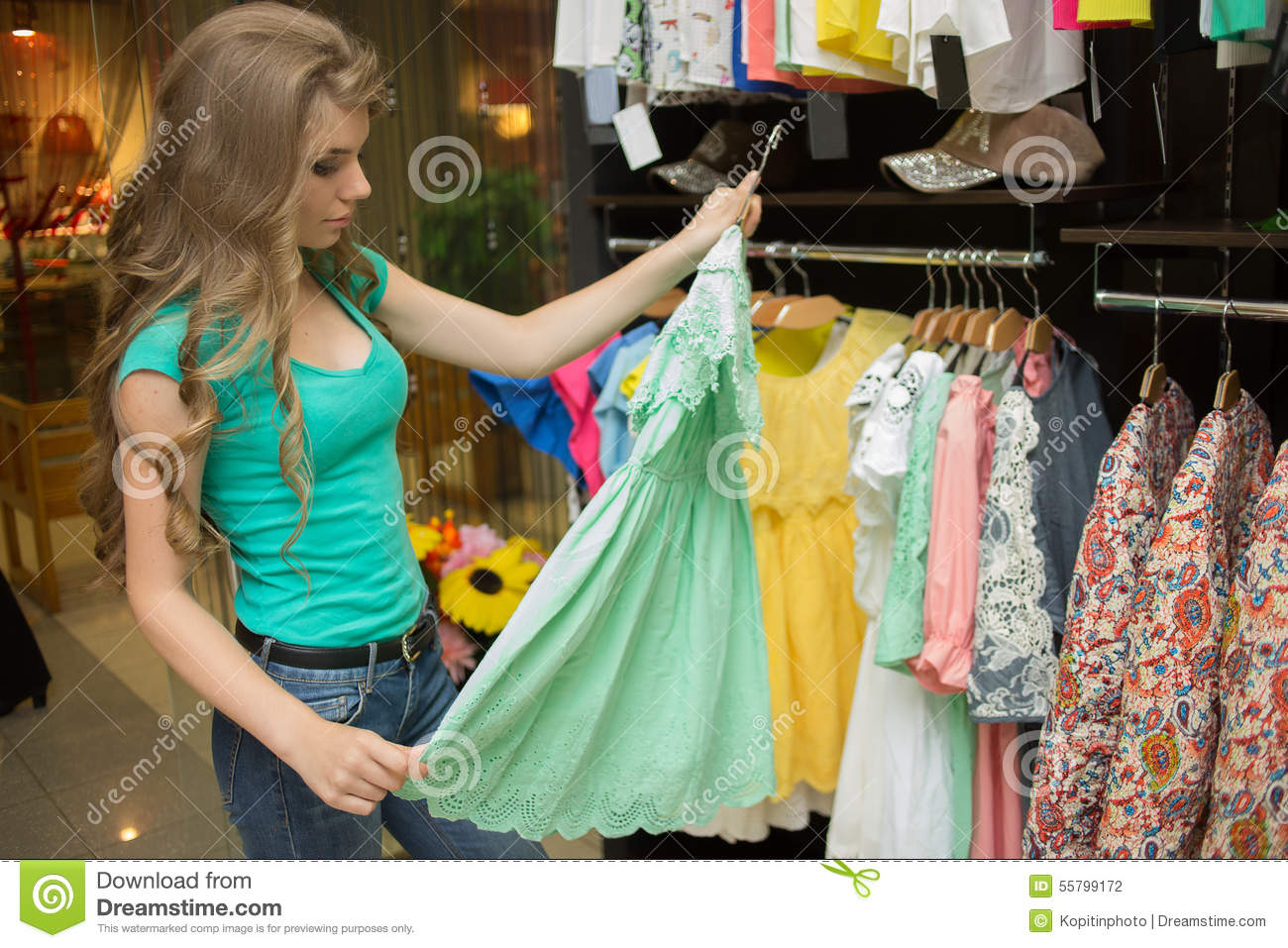 Elegant woman choosing dress in retail store