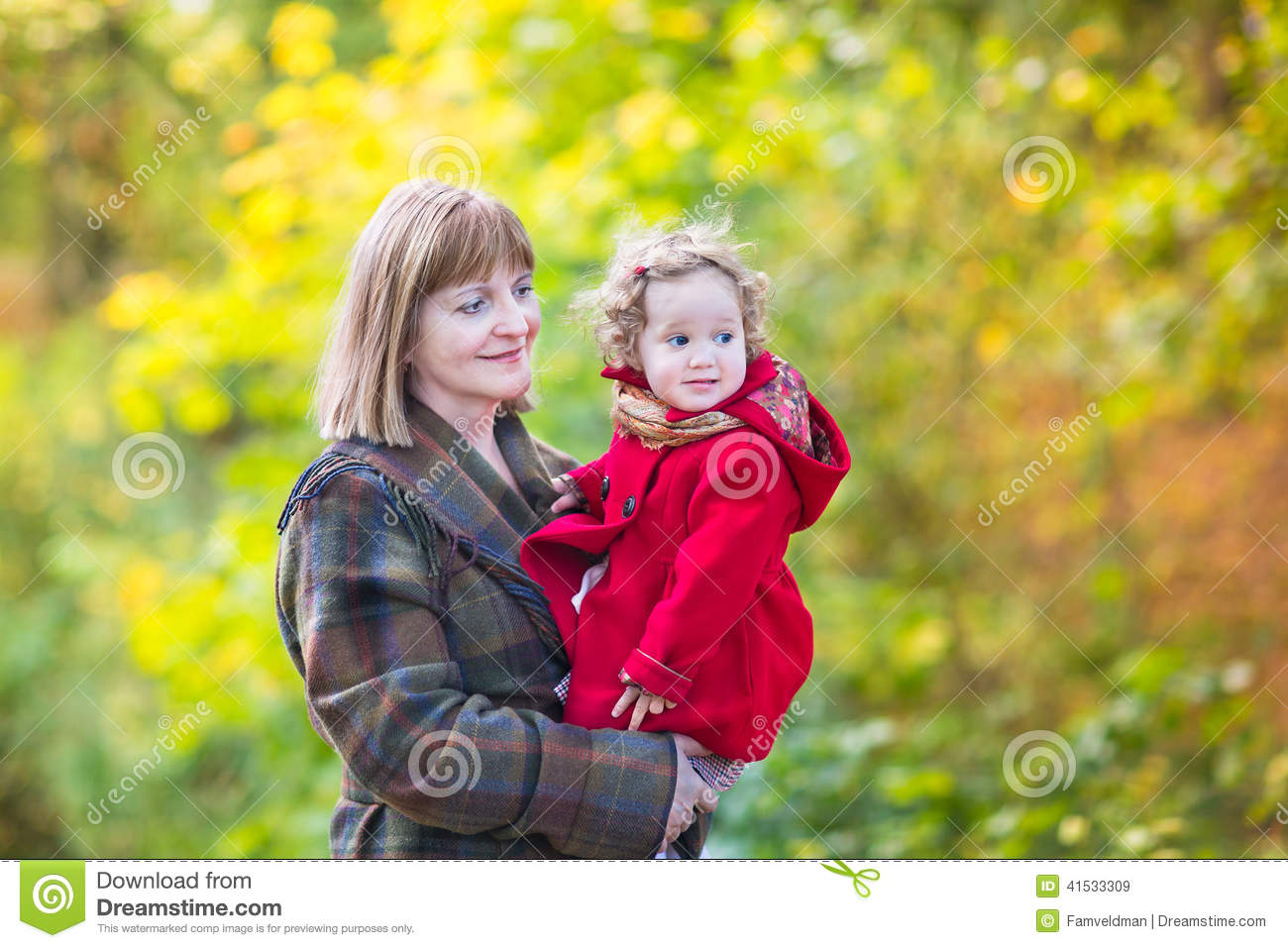 Elegant woman with little toddler girl in autumn park