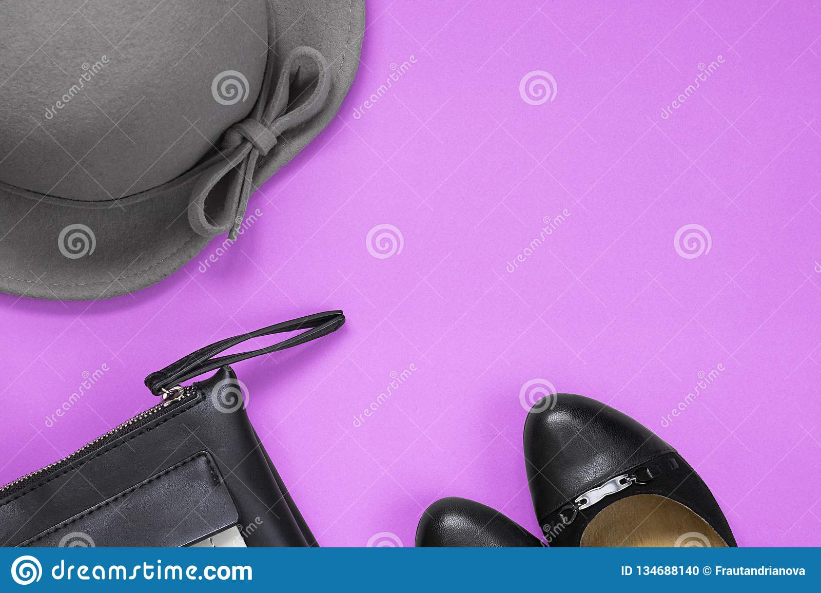 Woman`s accessories for autumn. Black leather purse, black shoes and grey hat. Copy space for text