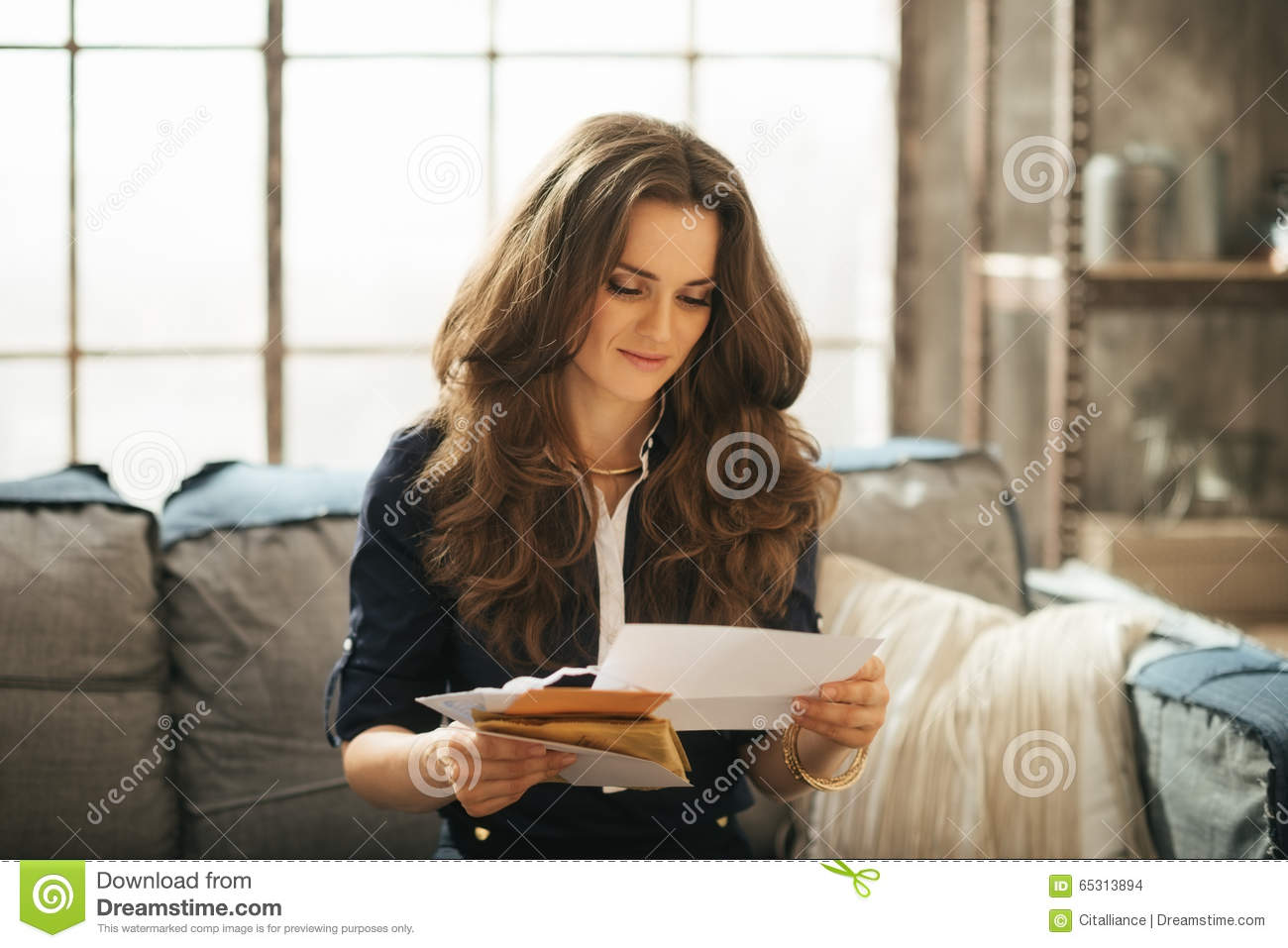 Elegant woman is sitting on couch and reading correspondence
