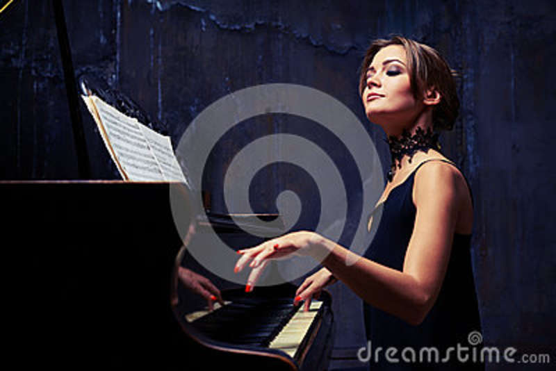 Elegant woman starts piano performance while sitting isolated in
