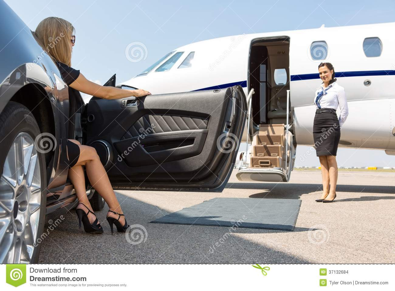 Elegant women stepping out of car parked in front of private plane and