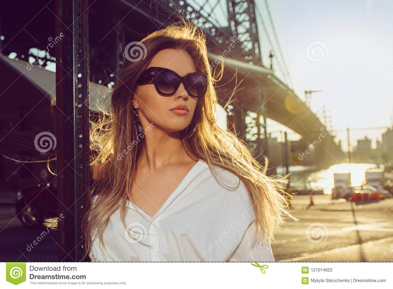 Elegant woman wearing sunglasses in the city at hot summer dayю