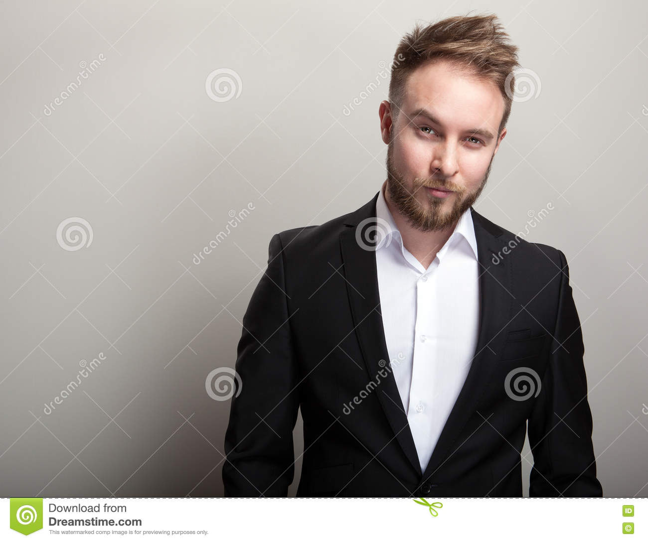 Elegant young handsome bearded man in classic black costume & white shirt