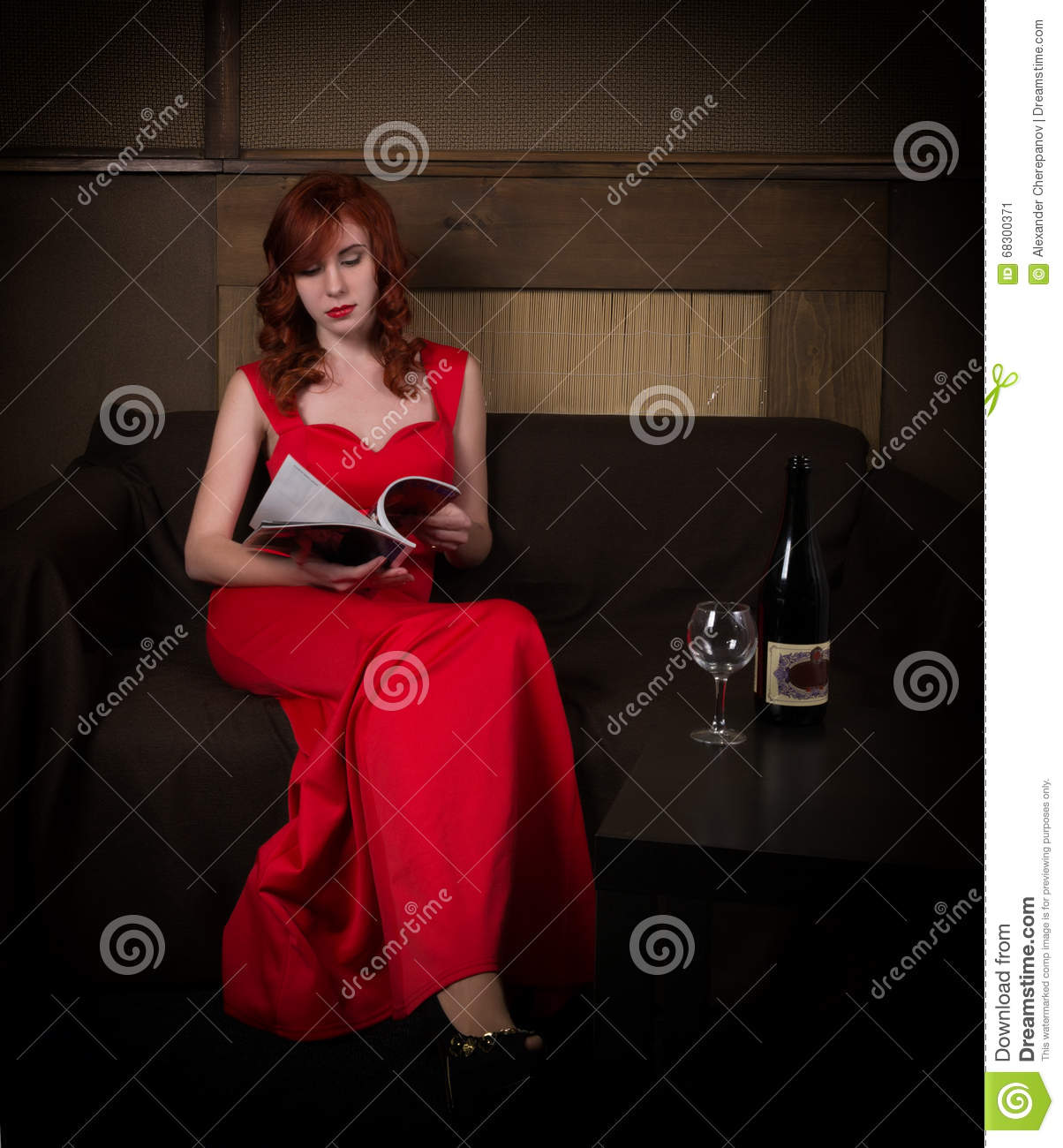 Elegant young redhead woman in a red dress, reads glamor magazine, having a glass of red wine.