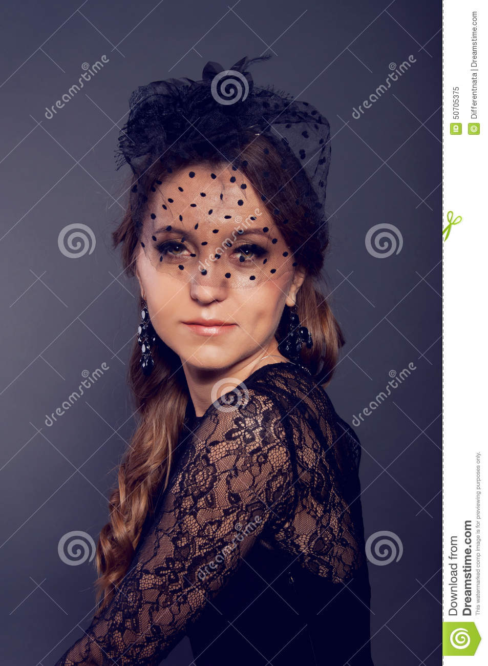 132831856ae2c Elegant young woman in black lace dress and black veil hat with long curly  hair. Retro style.