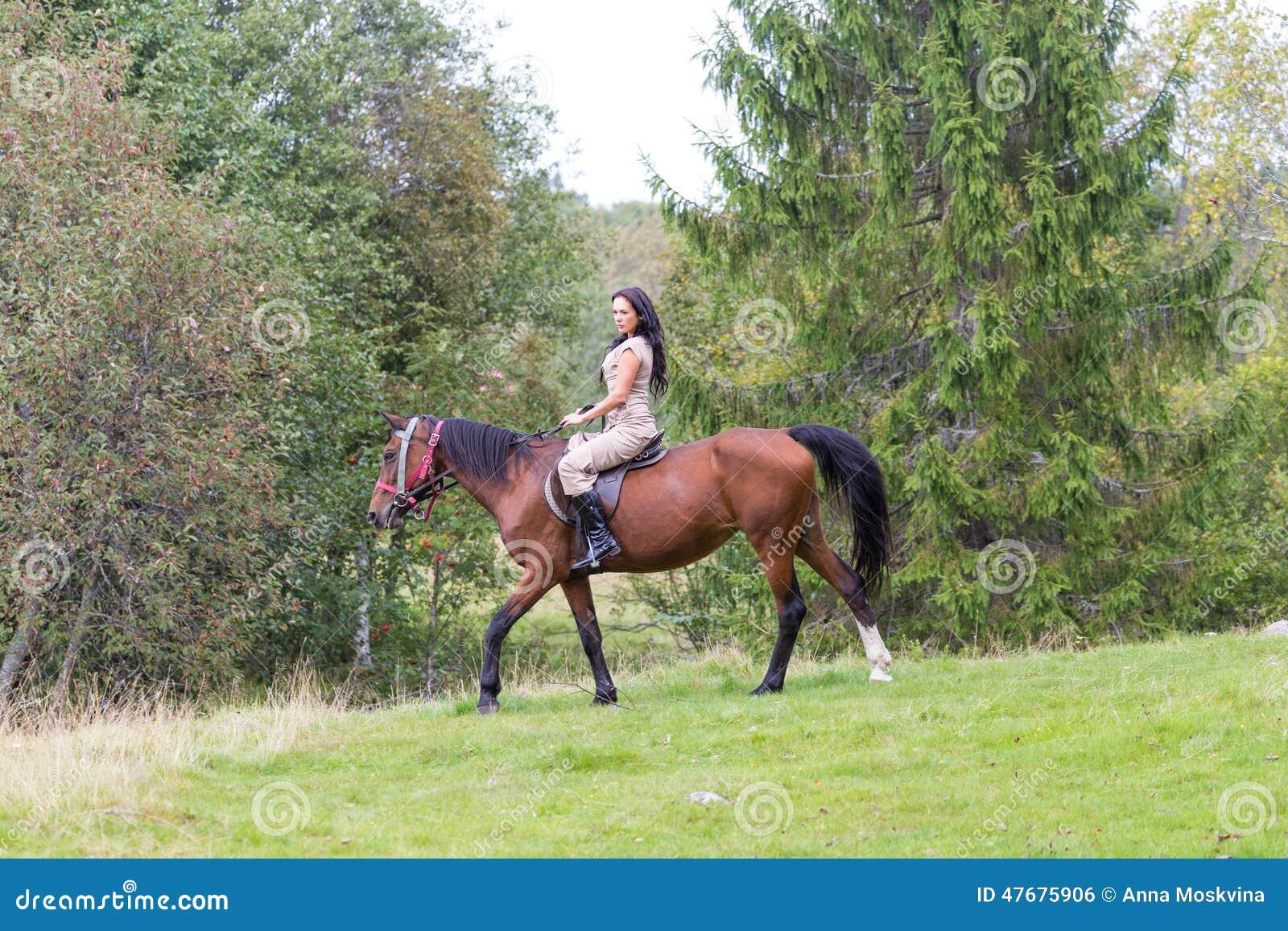 Elegante attraktive Frau, die eine Pferdewiese reitet
