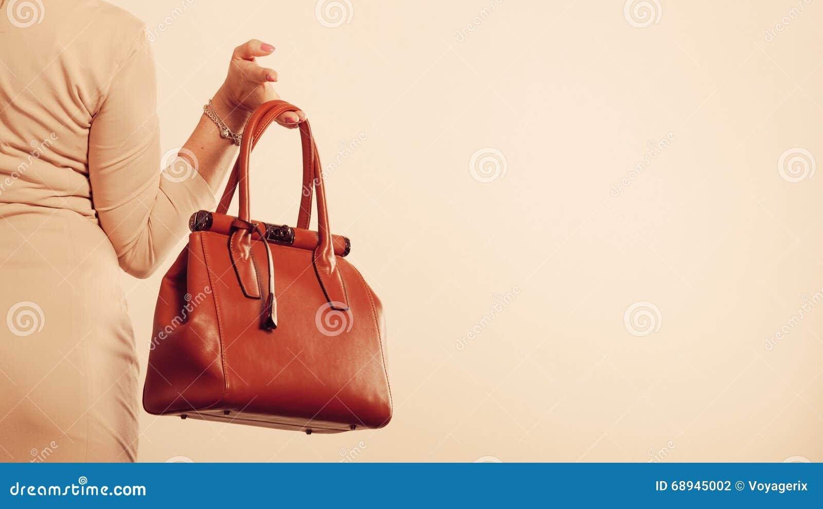 Elegante Frau hält braune Handtasche