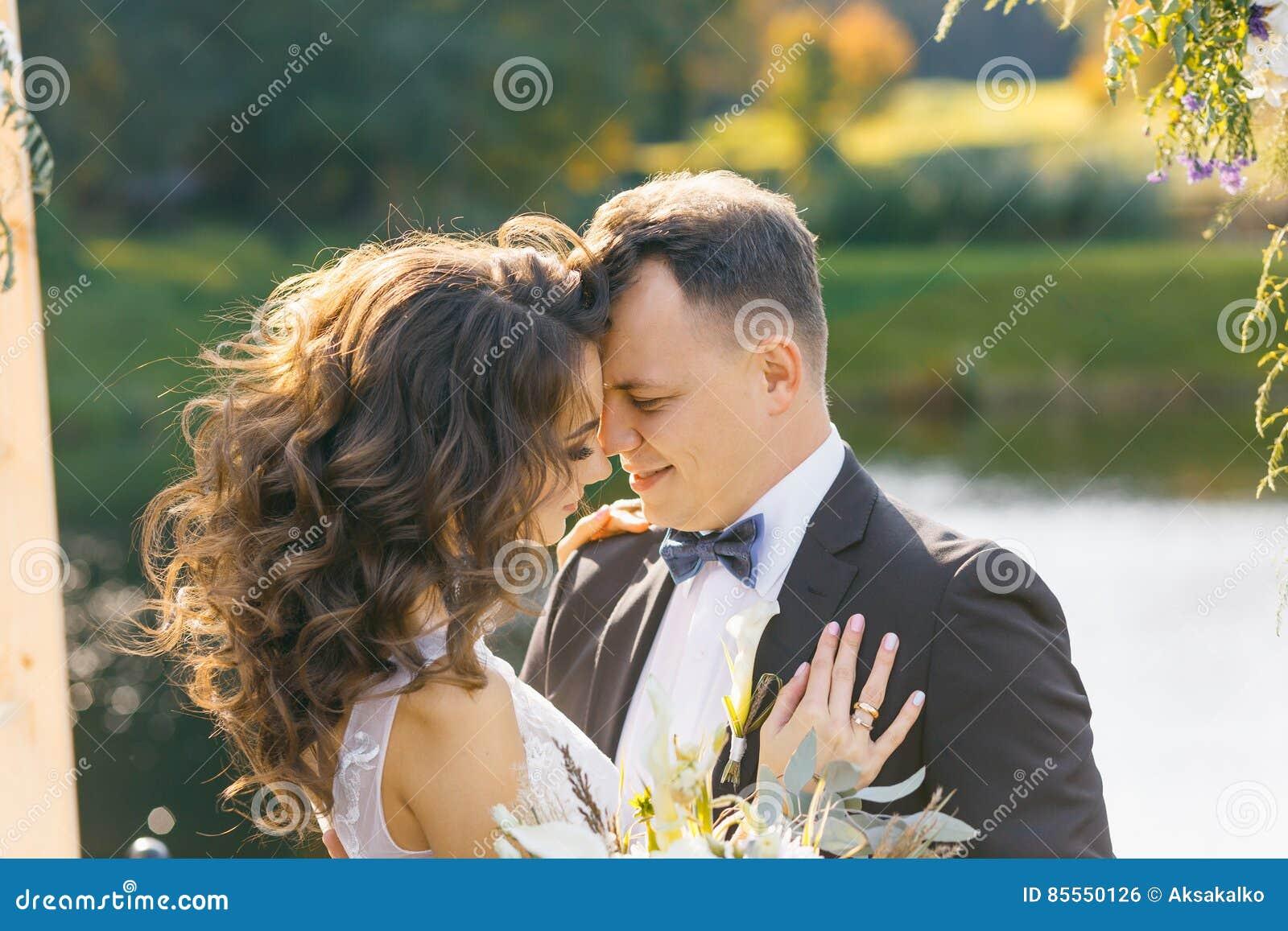 Elegante gelockte Braut und glücklicher Bräutigam draußen auf dem Hintergrund der See