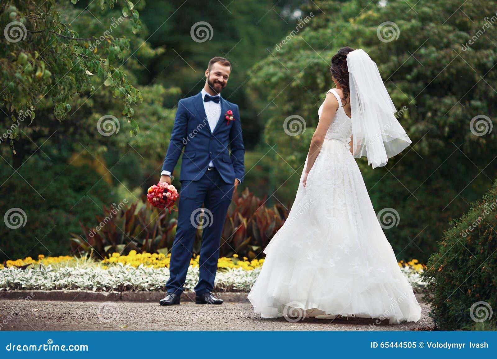 Elegante gelukkige bruid die in mooie kleding naar het glimlachen van g lopen