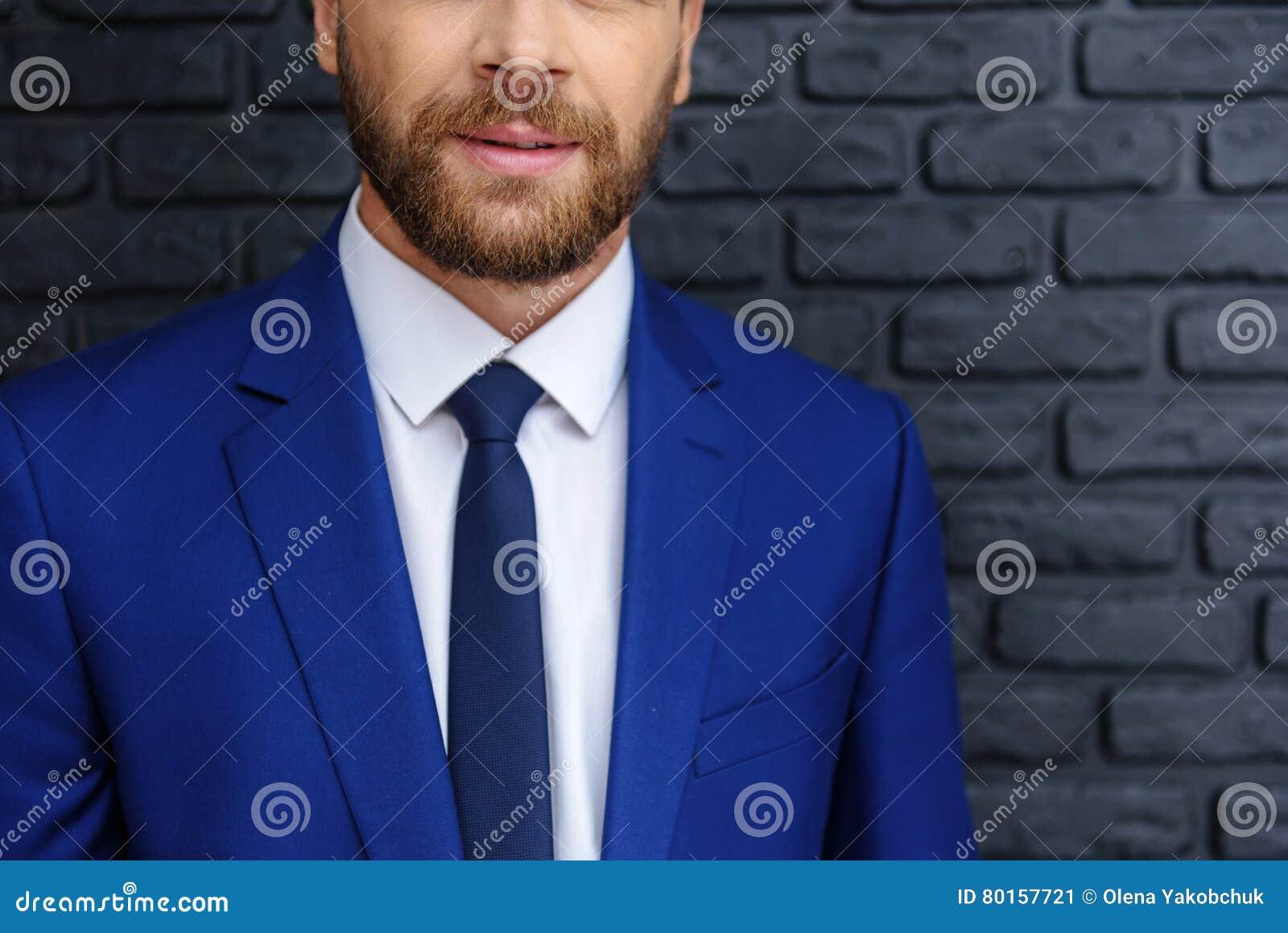 Elegante gelukkige kerel tegen donkere achtergrond