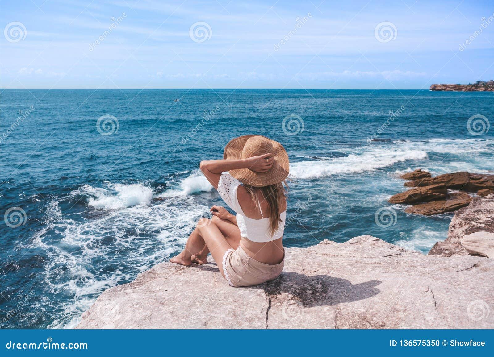 Elegante jonge vrouwenzitting door de oceaan