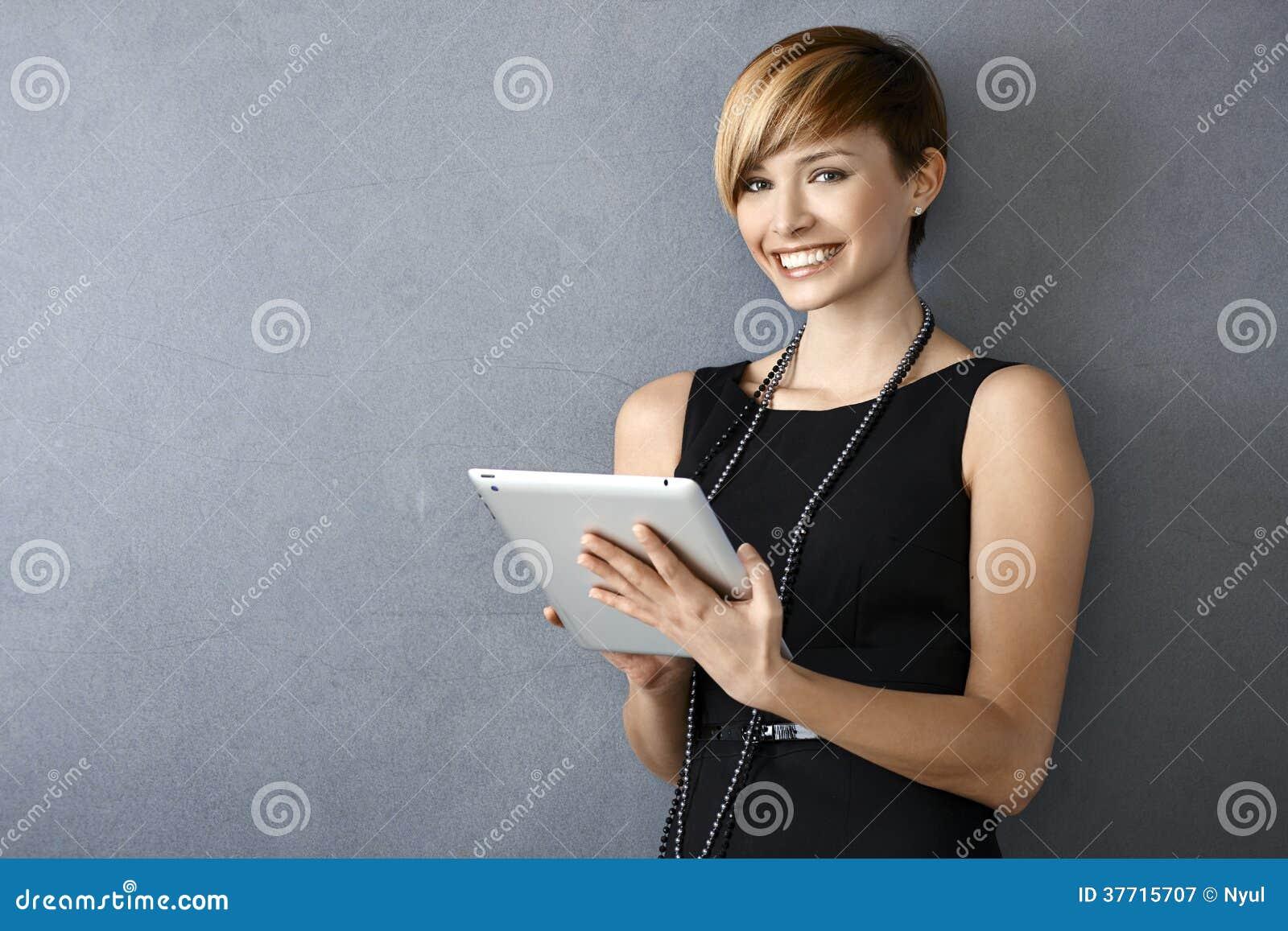 Elegante junge Frau, welche die Tablette sich lehnt zur Wand verwendet