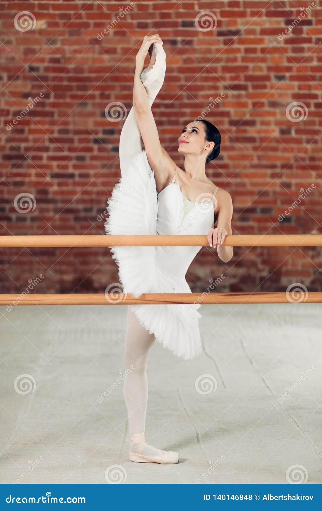 Elegante junge lächelnde Frau im Ballettröckchen, das Beine in der Tanzklasse ausdehnt