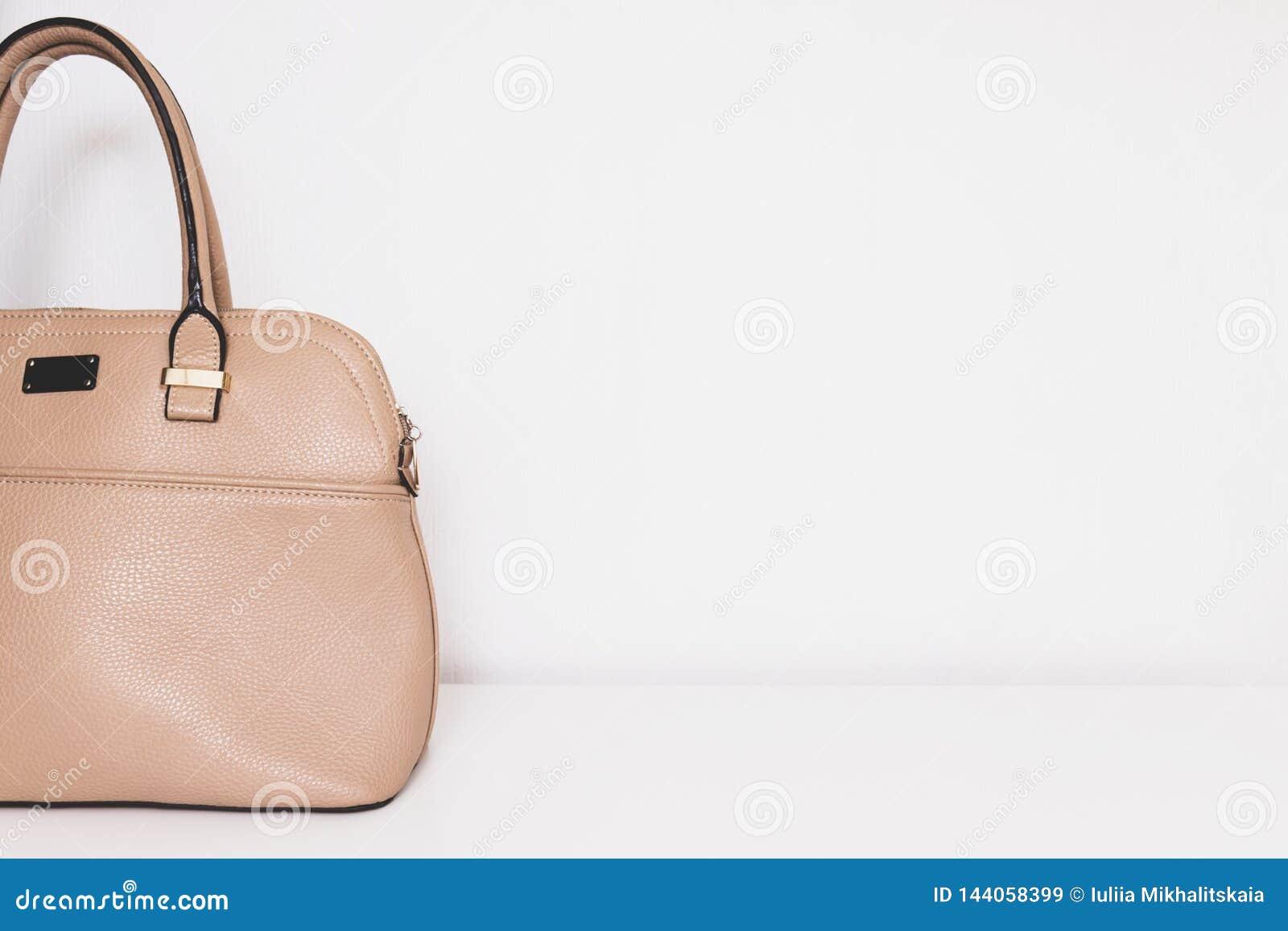 Elegante modieuze formele beige leerhandtas voor bedrijfsvrouw op witte achtergrond, in minimalistic luxestijl met