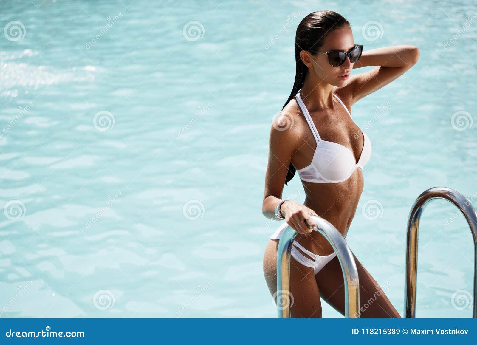 Elegante sexy Frau im weißen Bikini auf dem sonnen-gebräunten dünnen und formschönen Körper wirft nahe dem Swimmingpool auf