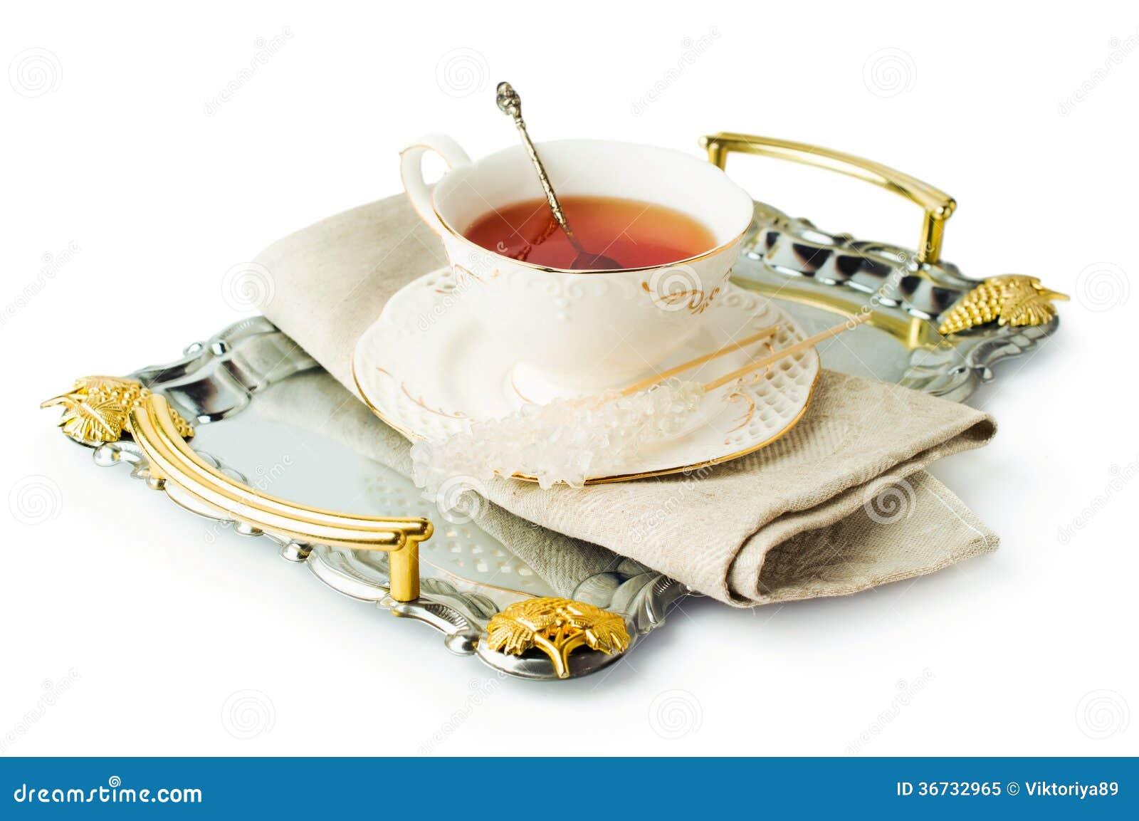Elegante theekop op een dienblad met suiker op een stok