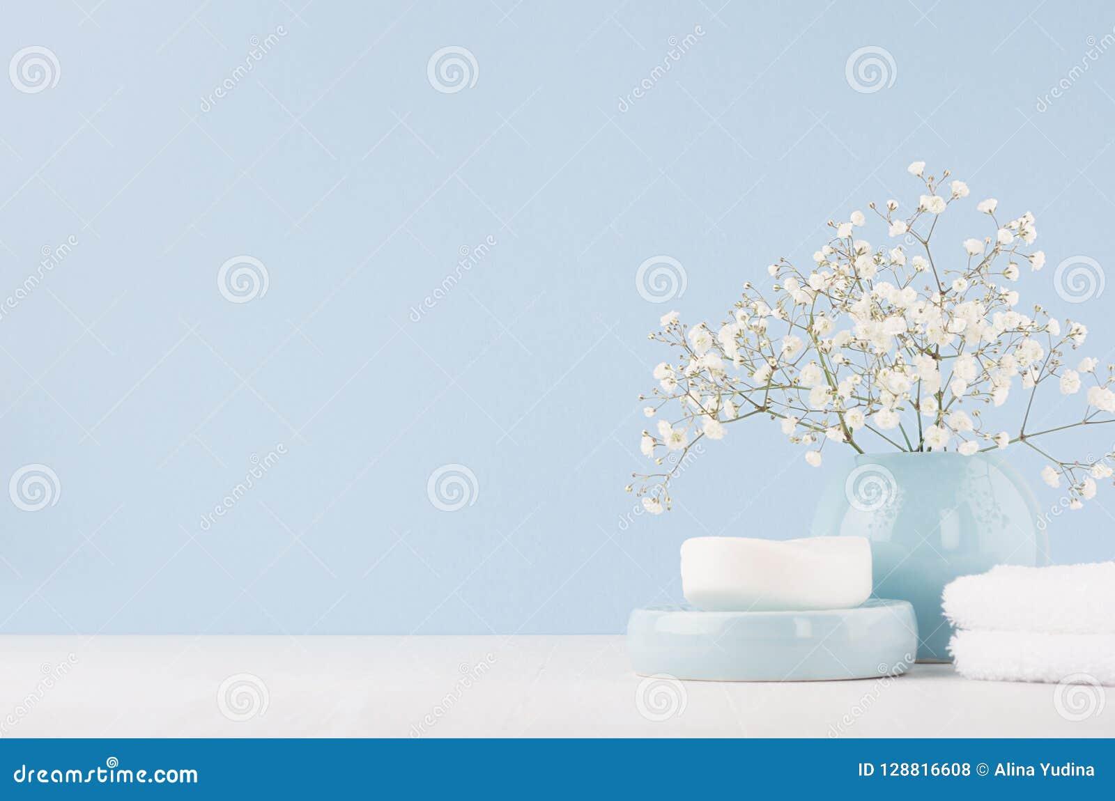Elegante toebehoren voor toilettafel - zachte pastelkleur blauwe ceramische kommen, witte bloemen, producten voor huid en lichaam