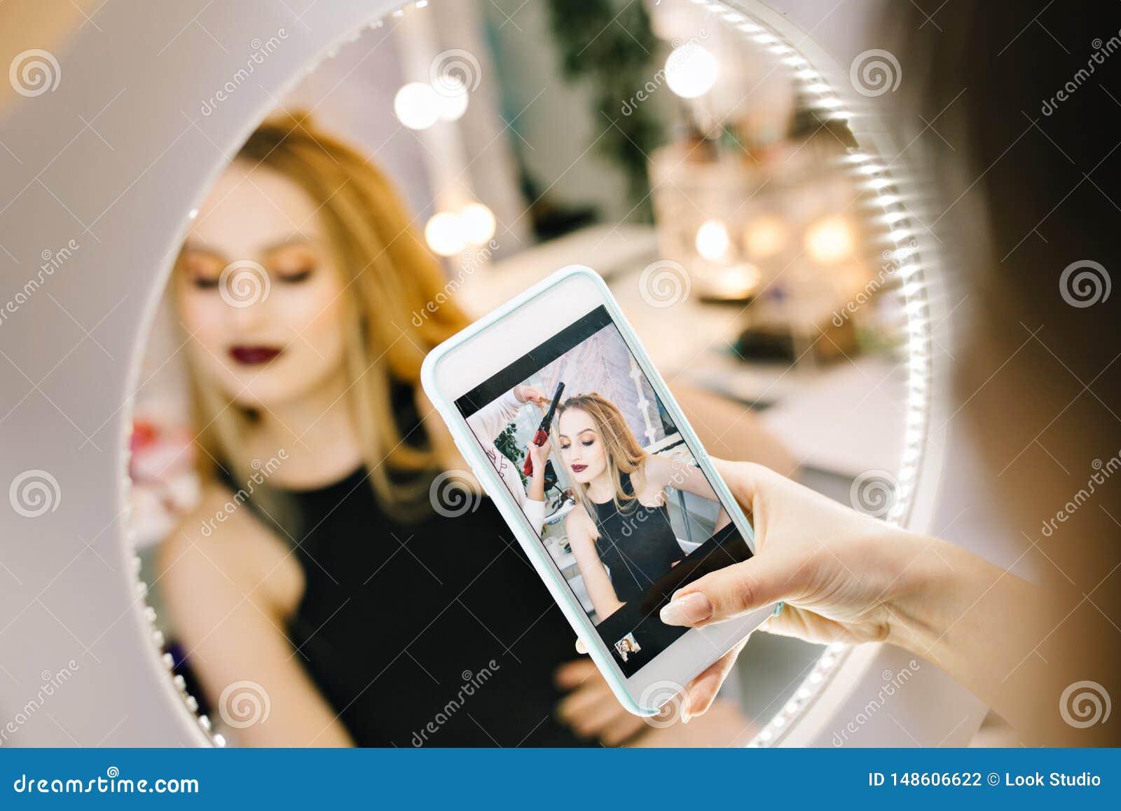 Elegante vrij jonge vrouw die foto op telefoon in spiegel maken tijdens het maken van kapsel in kappersalon stylish